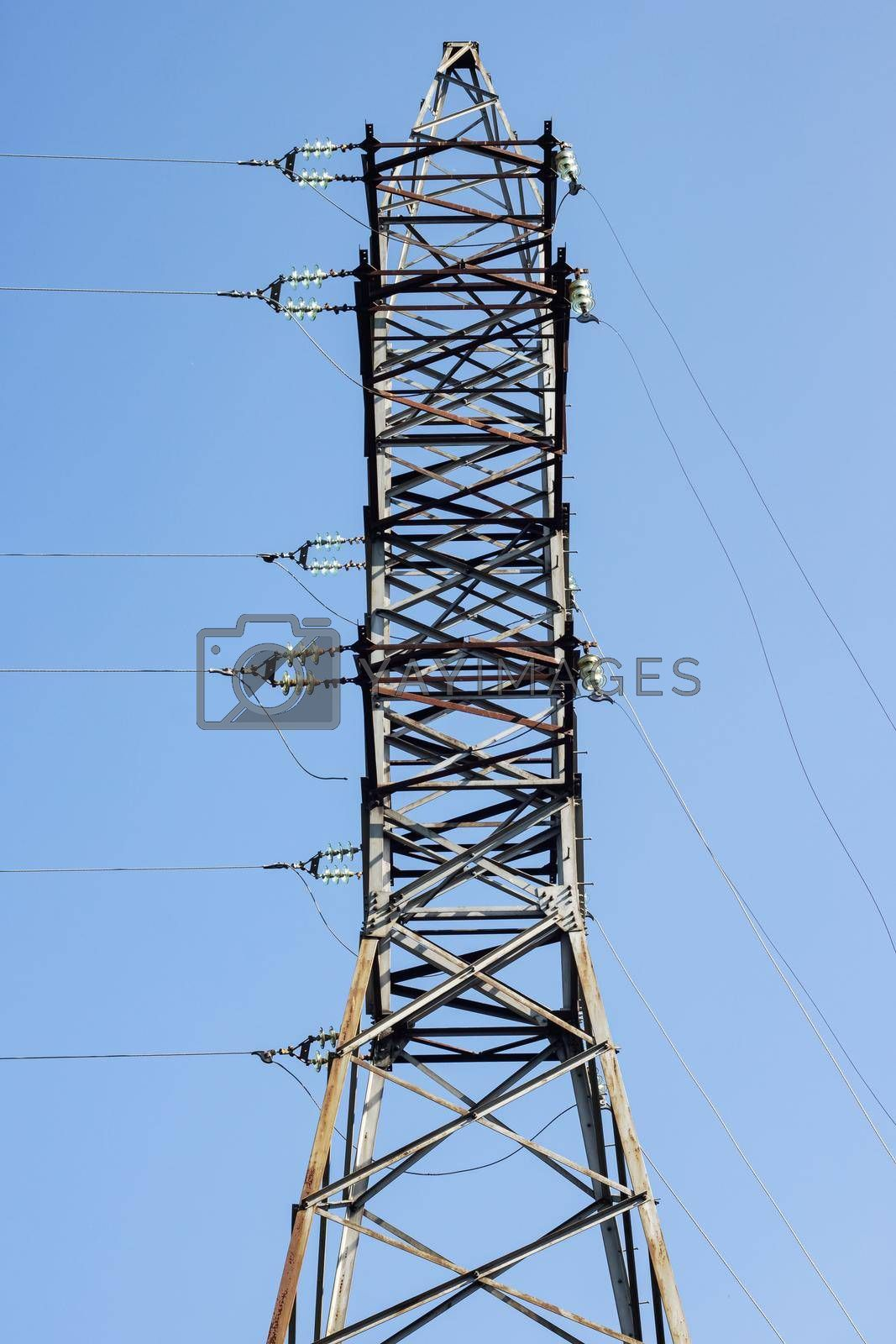Metal pole with electrical networks on a blue sky background close up