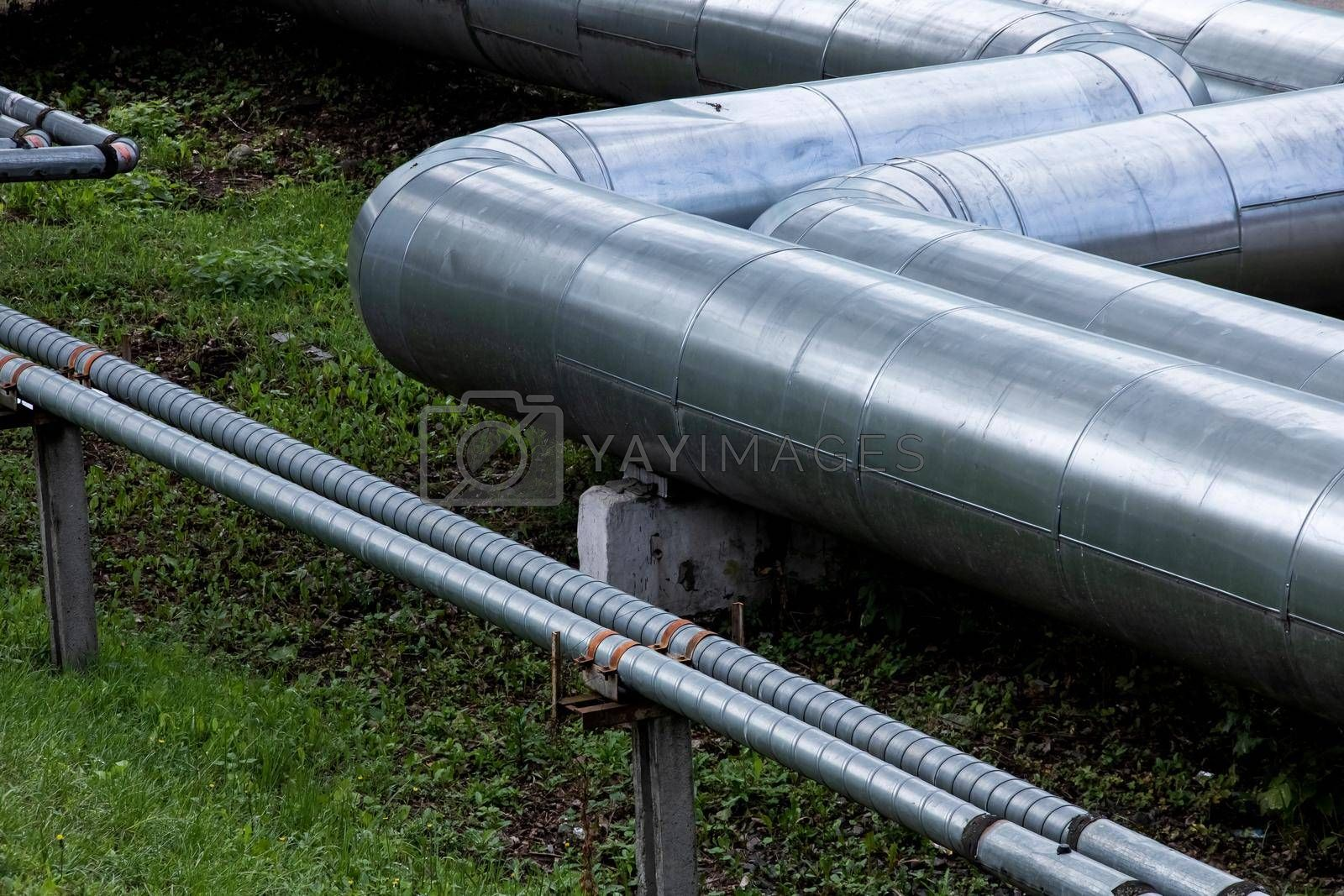 Metal water pipes above the ground close up, industrial elements