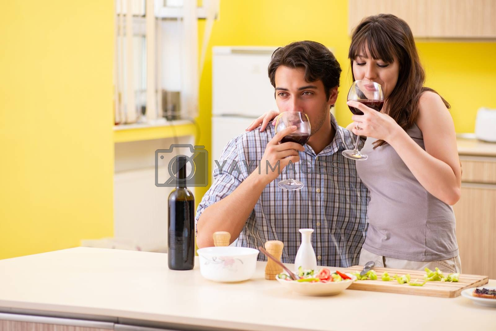 Young couple celebrating wedding anniversary at kitchen