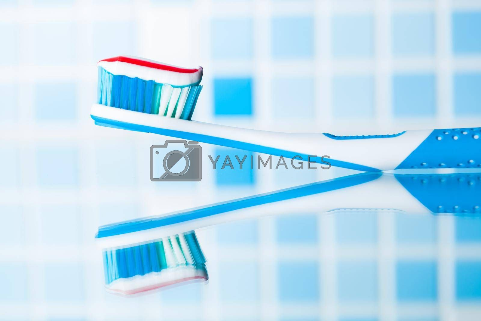 toothbrush with red stripe toothpaste and mirror reflection
