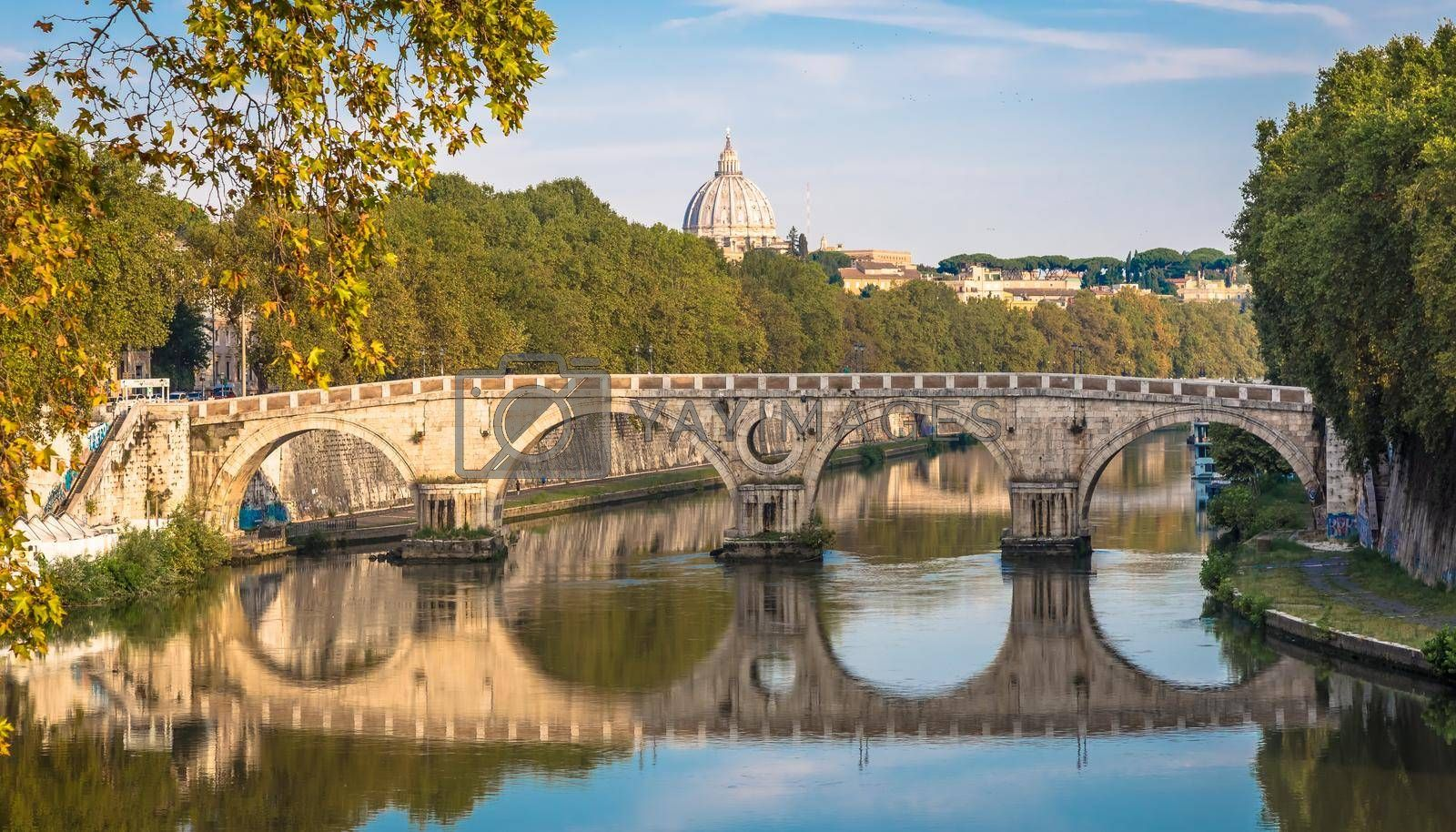Royalty free image of Bridge on Tiber river in Rome, Italy. Vatican Basilica cupola in background with sunrise light. by Perseomedusa