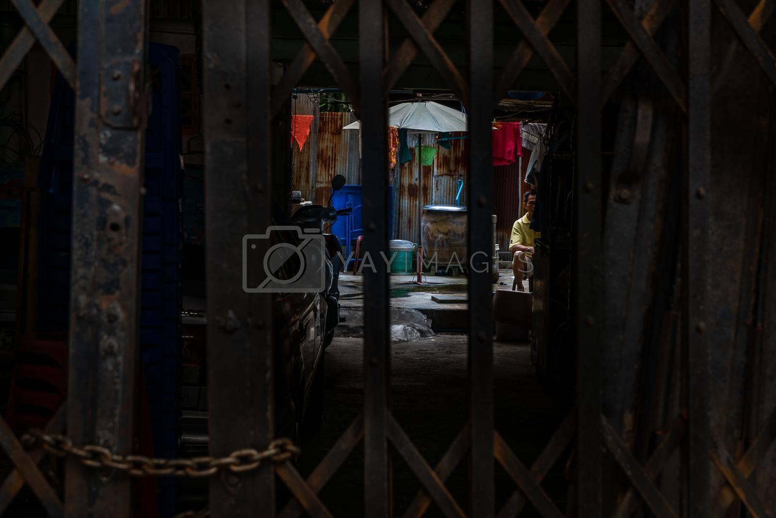 bangkok,Thailand - jun 29, 2019 : The ancient iron door that opened to see the interior where men were sitting behind the house. bangkok