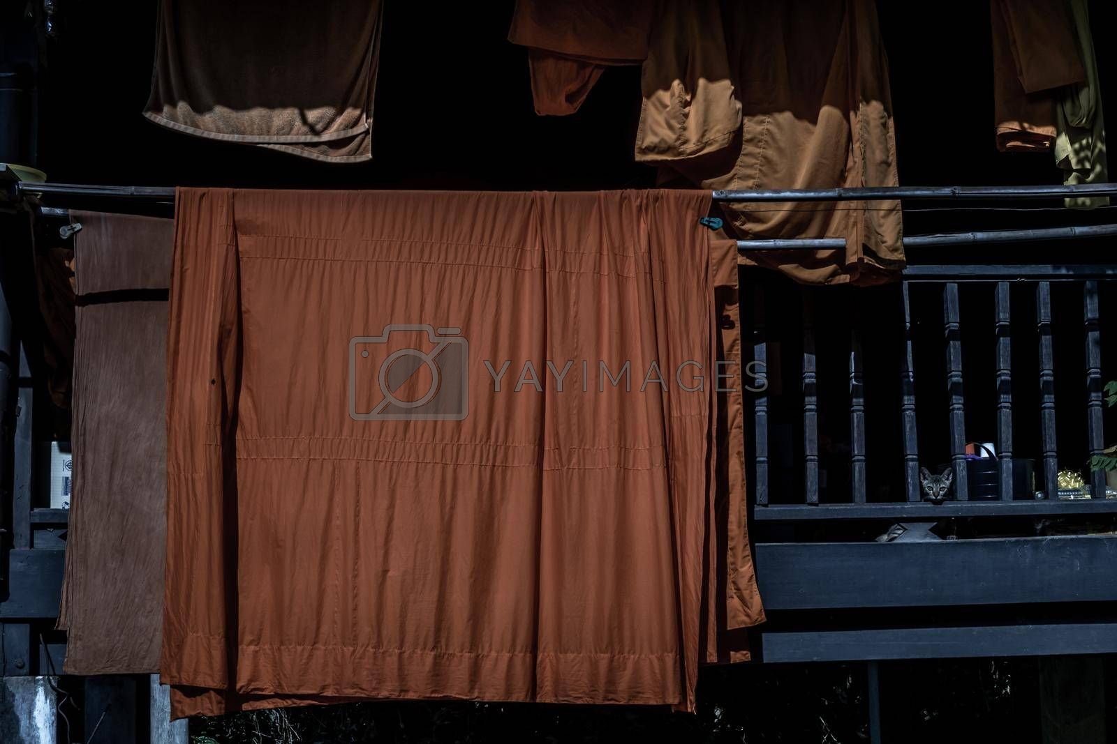 Bangkok, Thailand - 04 Dec 2019 : The vibrant orange robes worn by monks hung out to dry in the sun at Wat Chongnonsi.