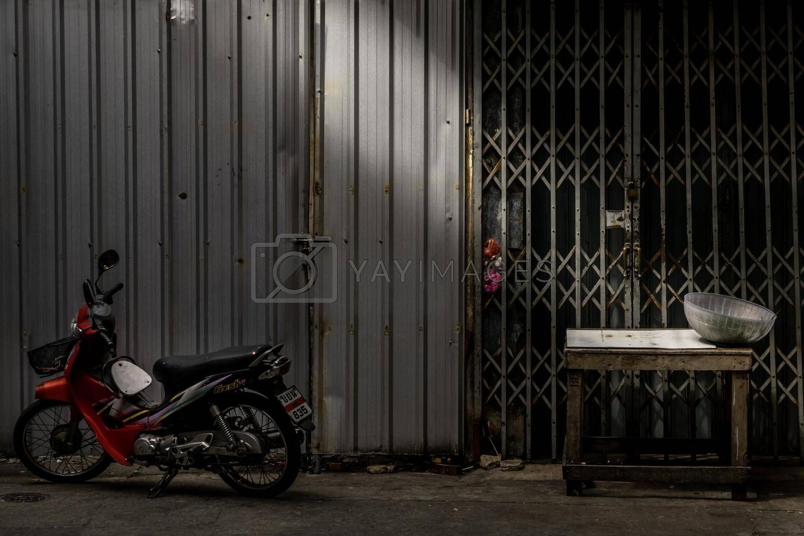 Bangkok, Thailand - Dec 7, 2019 : Motorcycle parked and old wooden table in front of ancient iron gate and Folding iron gates with locked.
