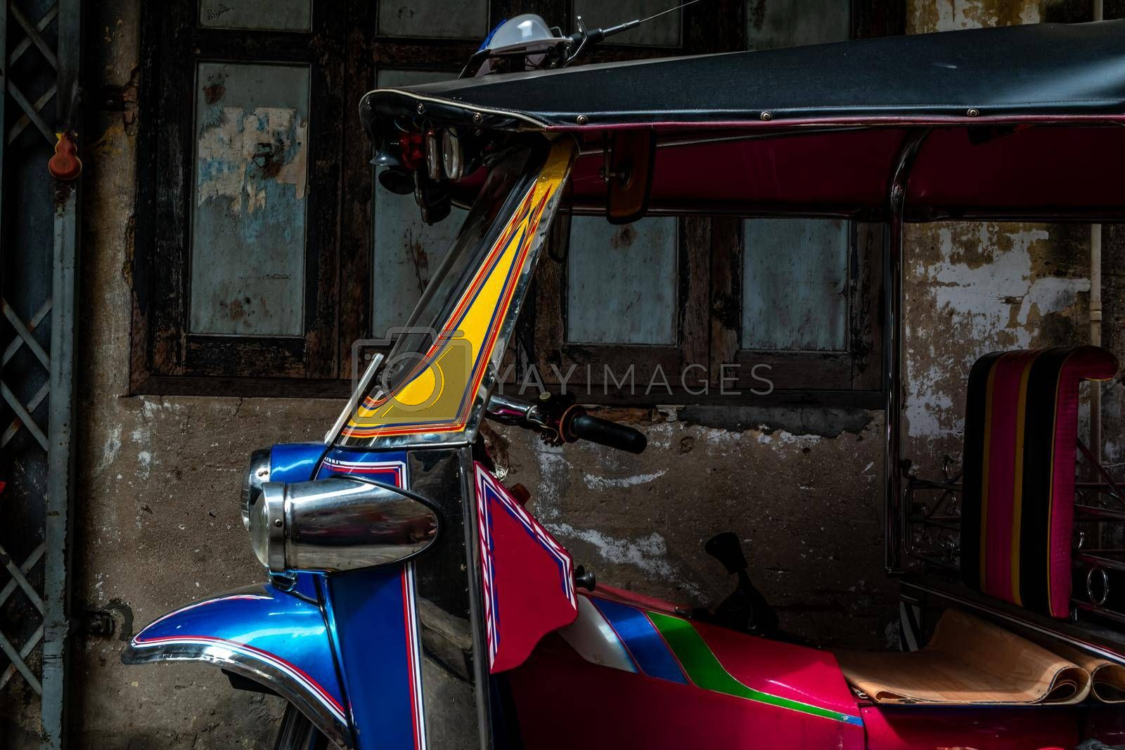 Bangkok, Thailand - Dec 7, 2019 : Famous blue Tuk Tuk, The front of thai traditional taxi with an old ancient wall behind.
