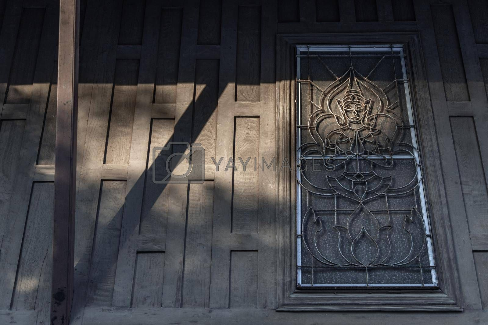 Bangkok, Thailand - Dec 9, 2019 :The shadow of the wooden beams shining on the window at ancient temple.
