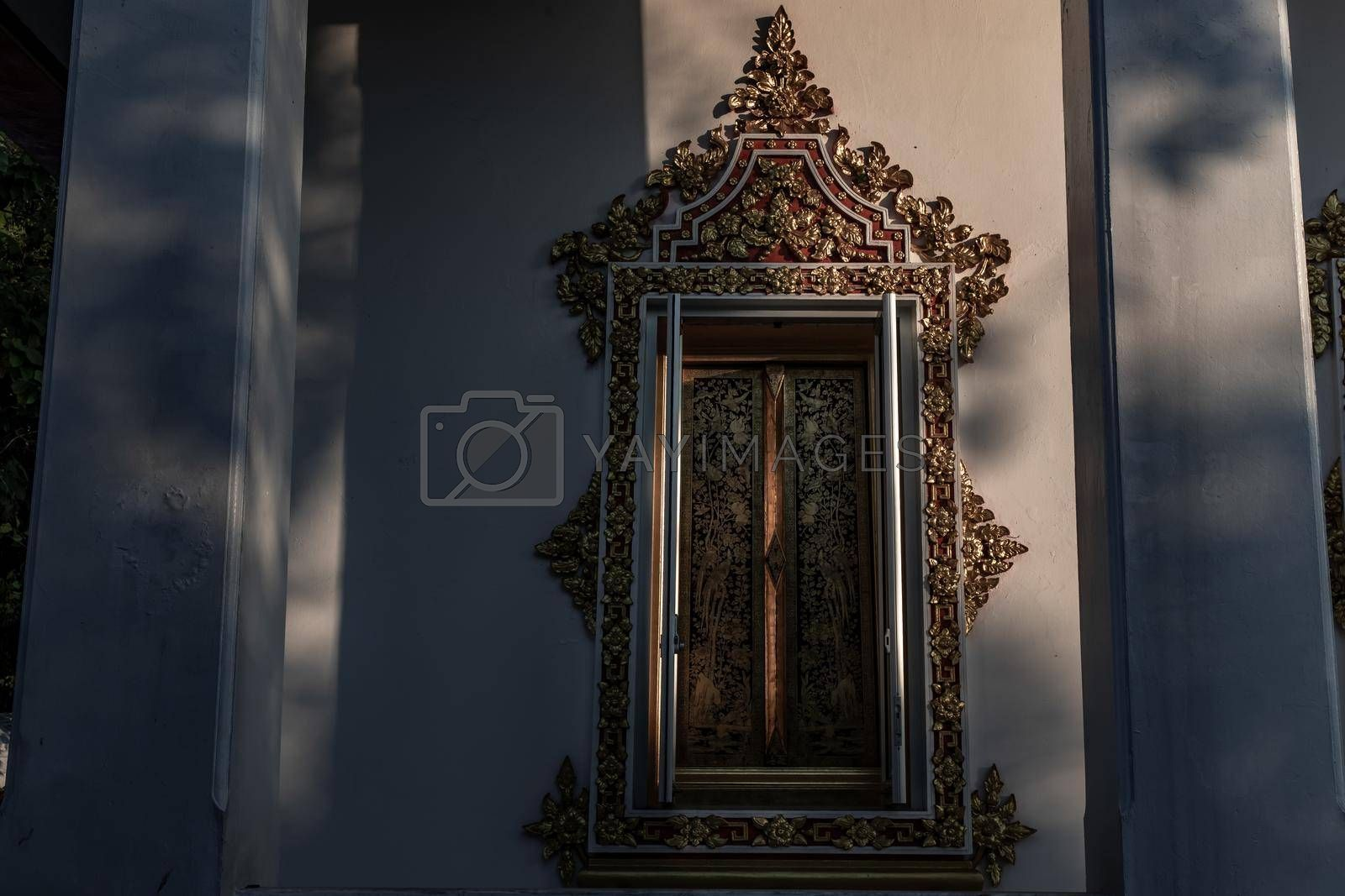 Bangkok, Thailand - Dec 9, 2019 : The light shines, creating light and shadow in the temple's architecture, Shadows and deep shade. Warm colours and contrasted light.