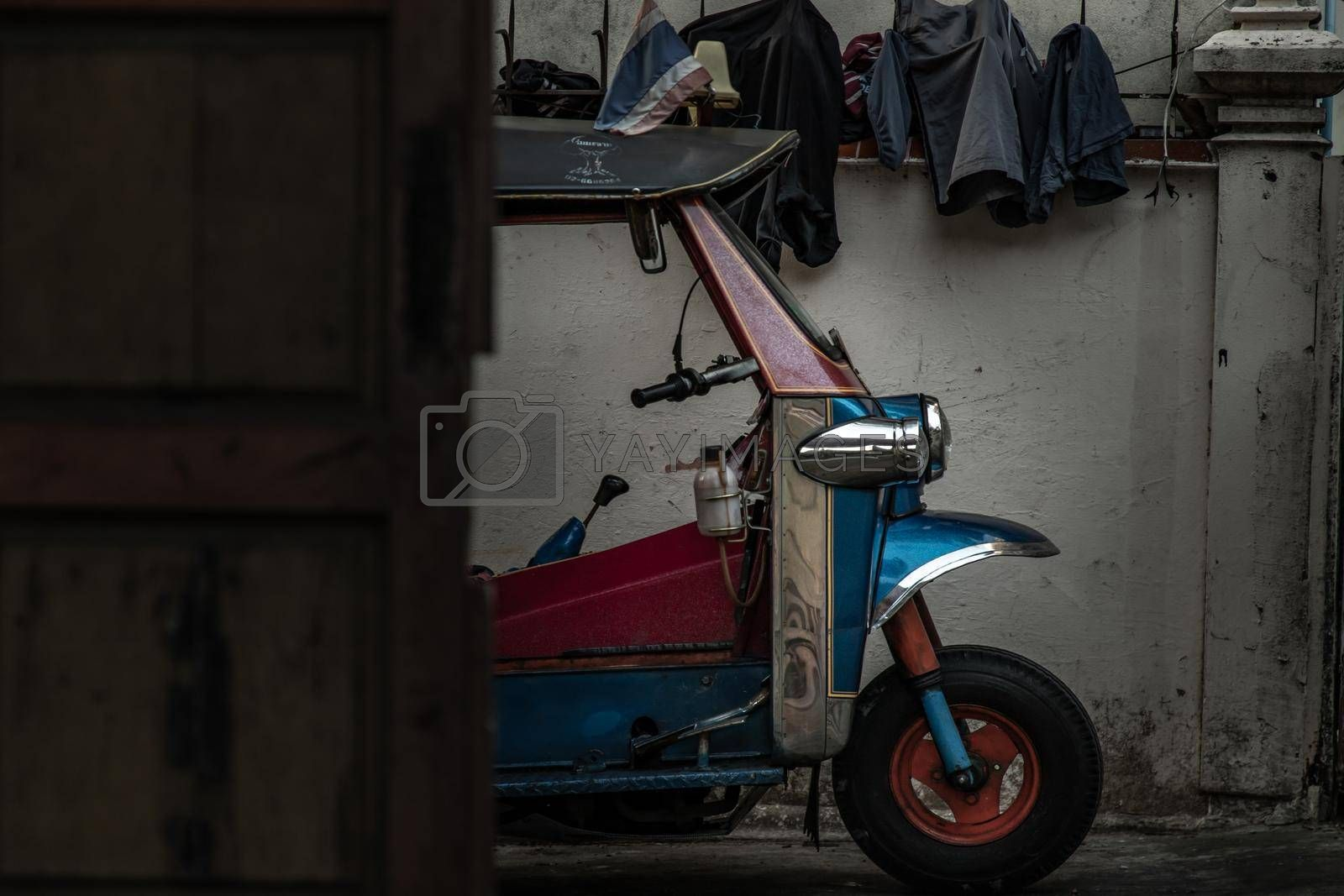 Bangkok, Thailand - Dec 9, 2019 : Famous blue Tuk Tuk, The front of thai traditional taxi with an old white wall behind.