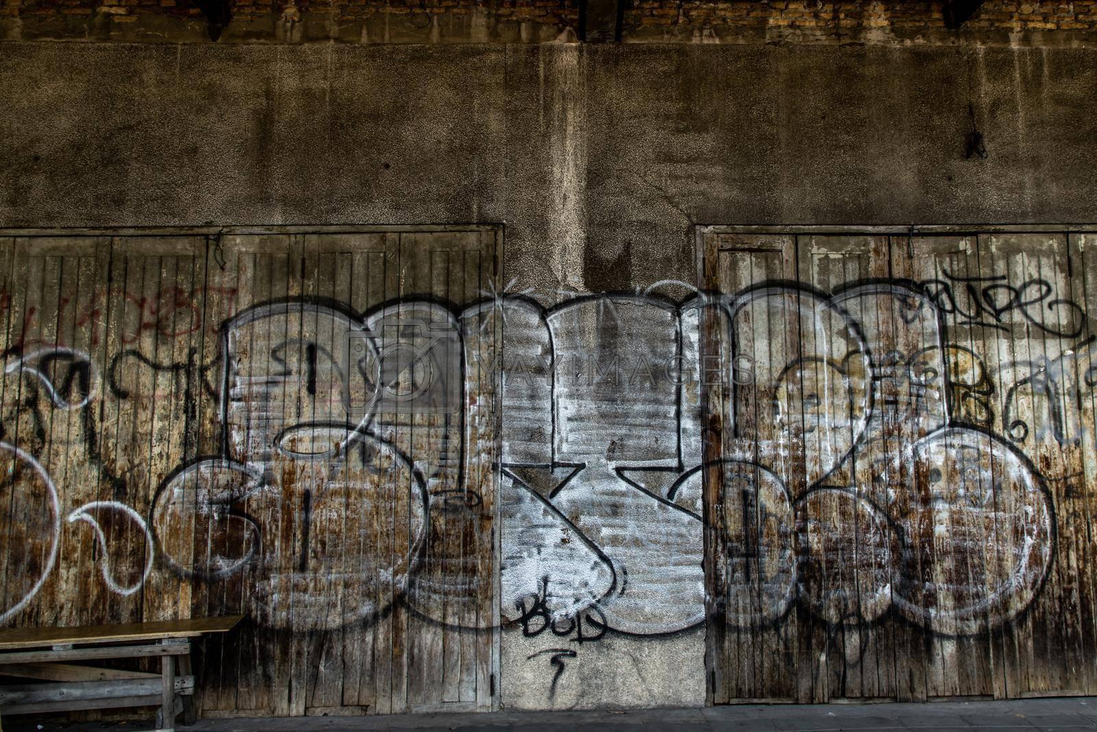 Bangkok, Thailand - Dec 12, 2019 : Wood vintage door on the old wall and graffiti painting.