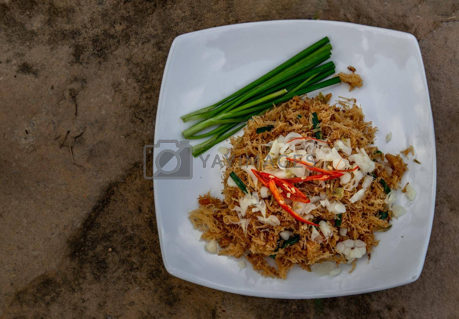 Asian eating food, Mee Grob is an sweet and sour crispy noodles, made from Thai rice noodle with sweet and sour sauce on white plate, Sweet & Sour Crispy Rice Noodles, Top view.