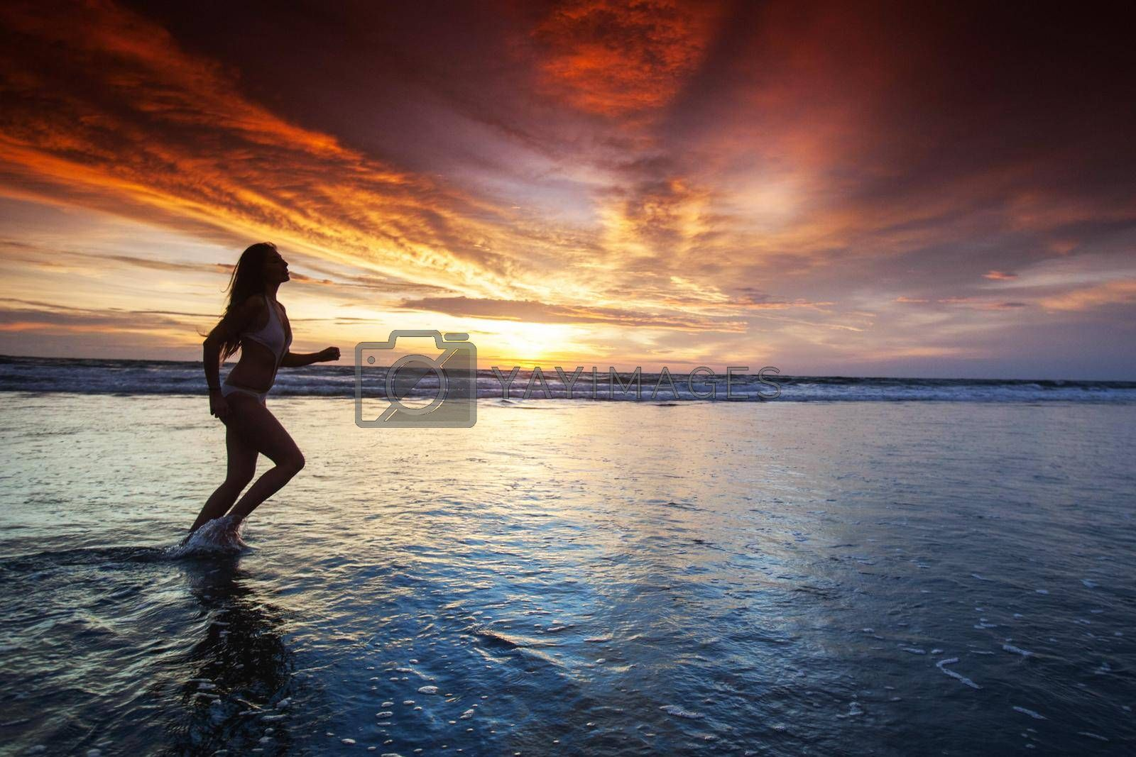 Royalty free image of Woman running by the ocean beach by Yellowj