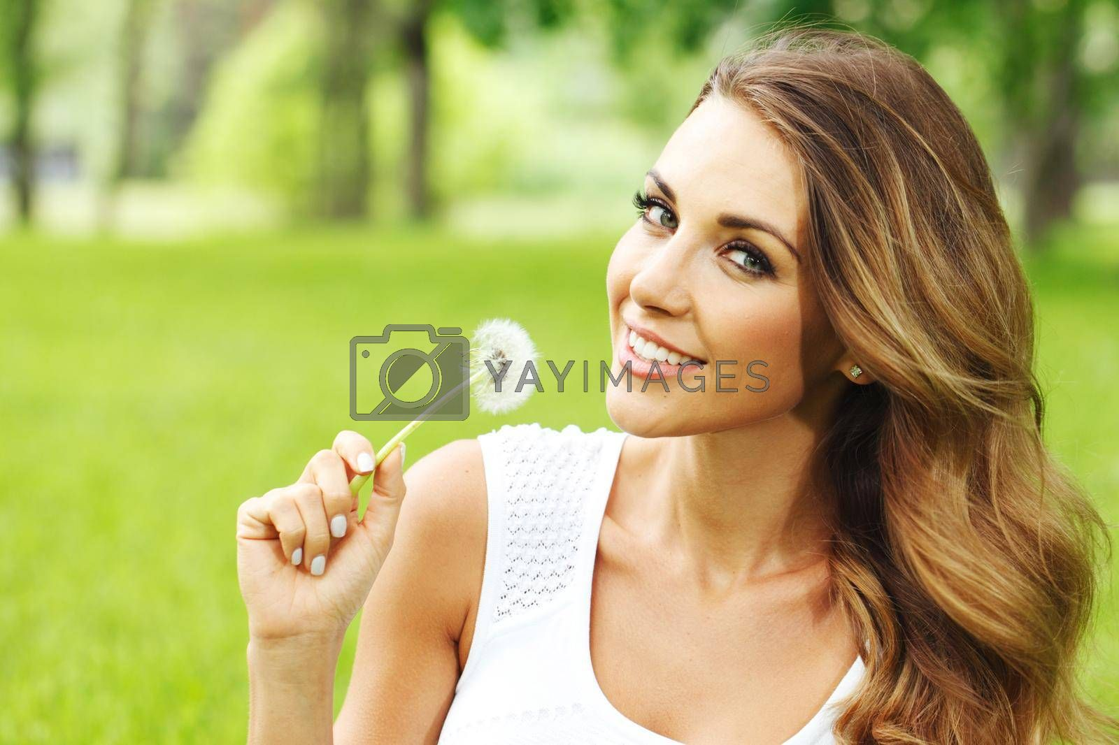 Royalty free image of Woman in park with dandelion by Yellowj