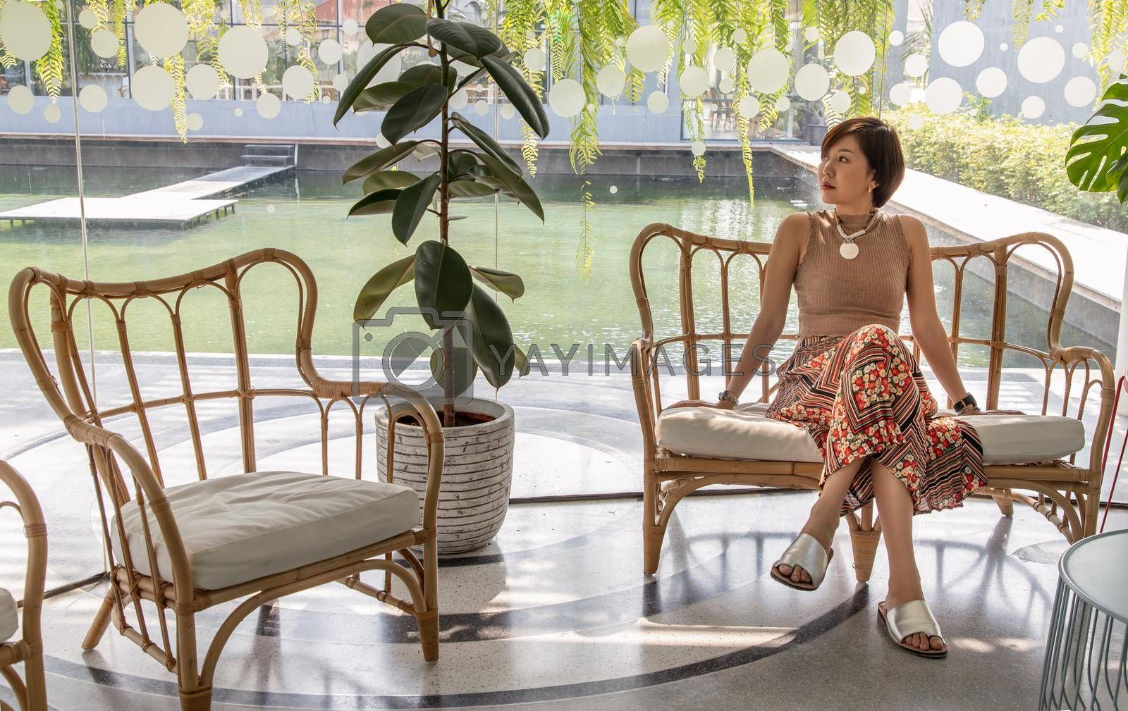 A young asian woman sitting and relax on cushion on rattan sofa  near glass window in living room. Selective focus.