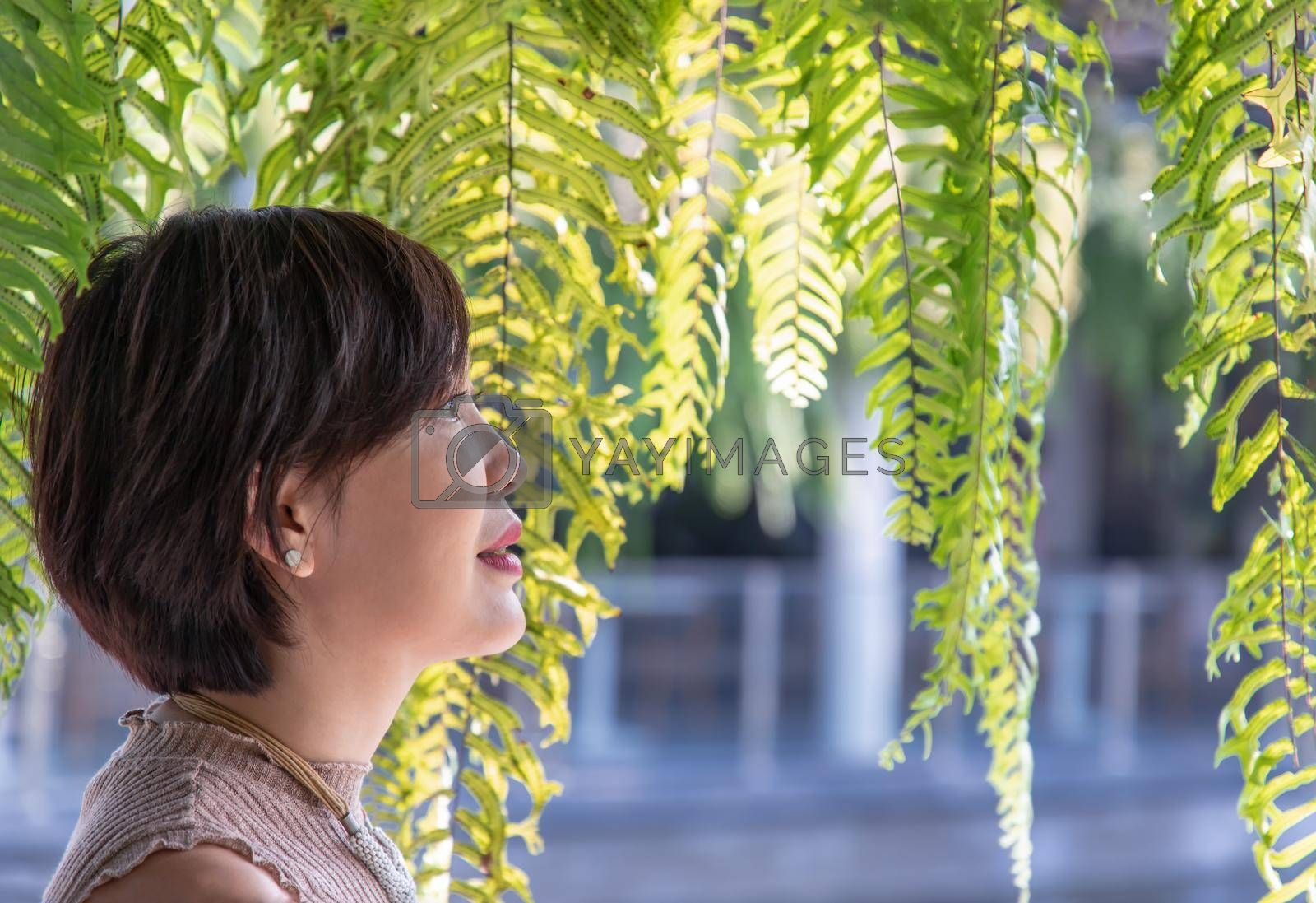 Portrait of a young Asian woman enjoy and relax on green ferns leaves background. Side view, Happy woman in nature concept, Selective focus.
