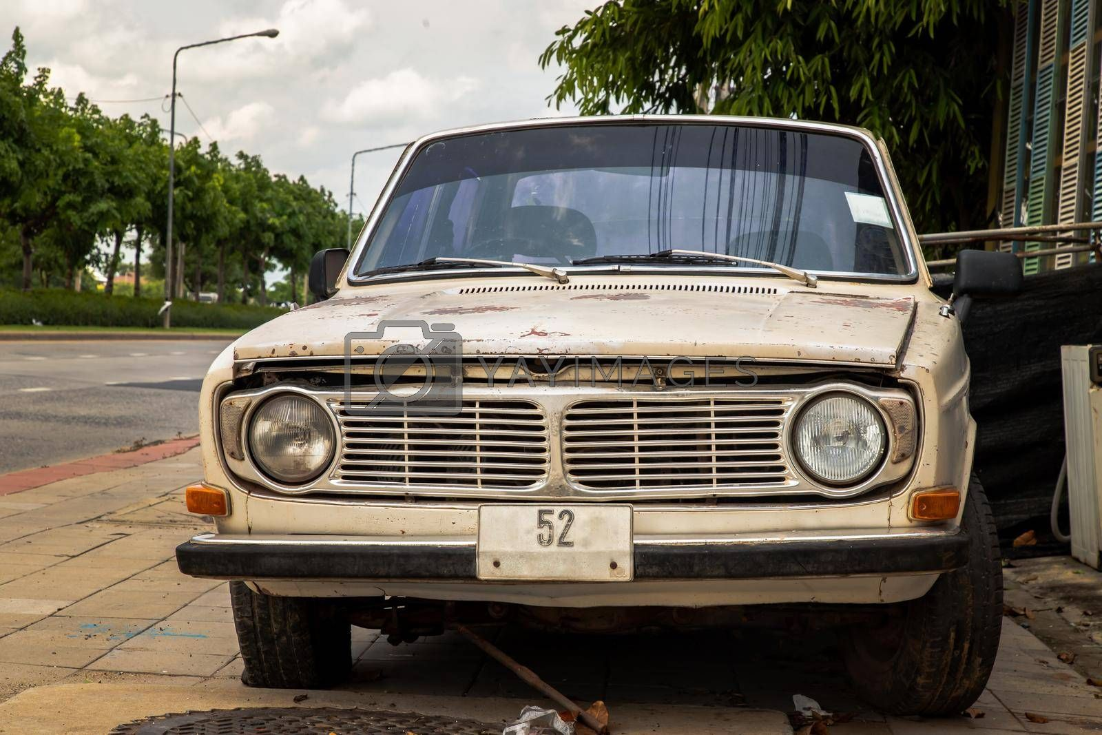 Bangkok,Thailand - May 20, 2021 : Front view of broken and old vintage car were left at the road side. Selective focus.