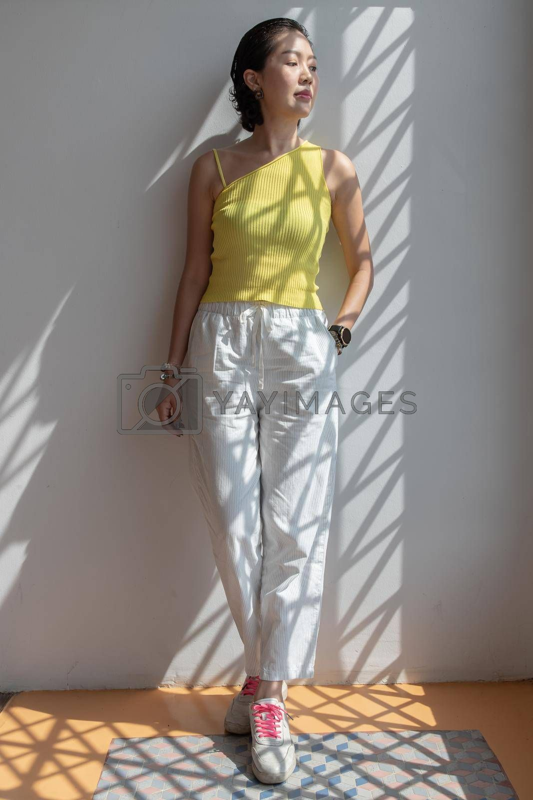 Young asian woman and short hair posing for take a photo on white wall. Selective focus.