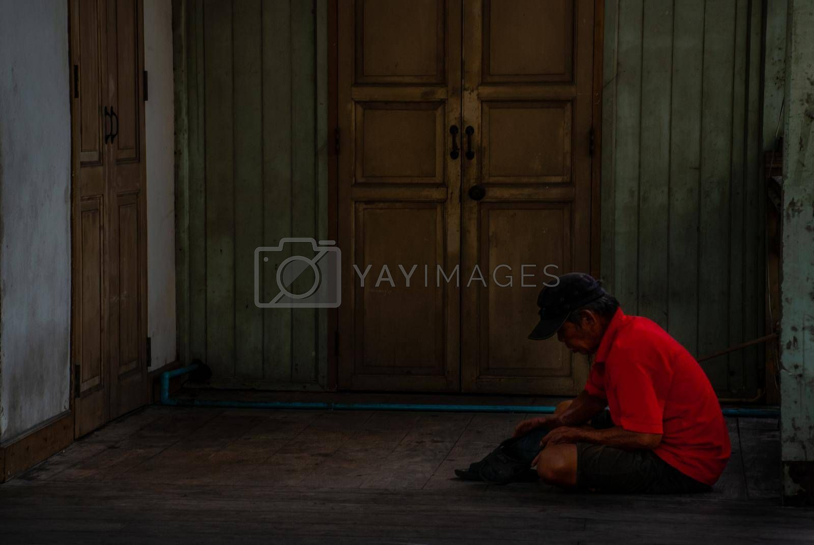 Nonthaburi, Thailand - JUL 21,2019 : Uncle sitting, fixing his shoes in front of the old room.