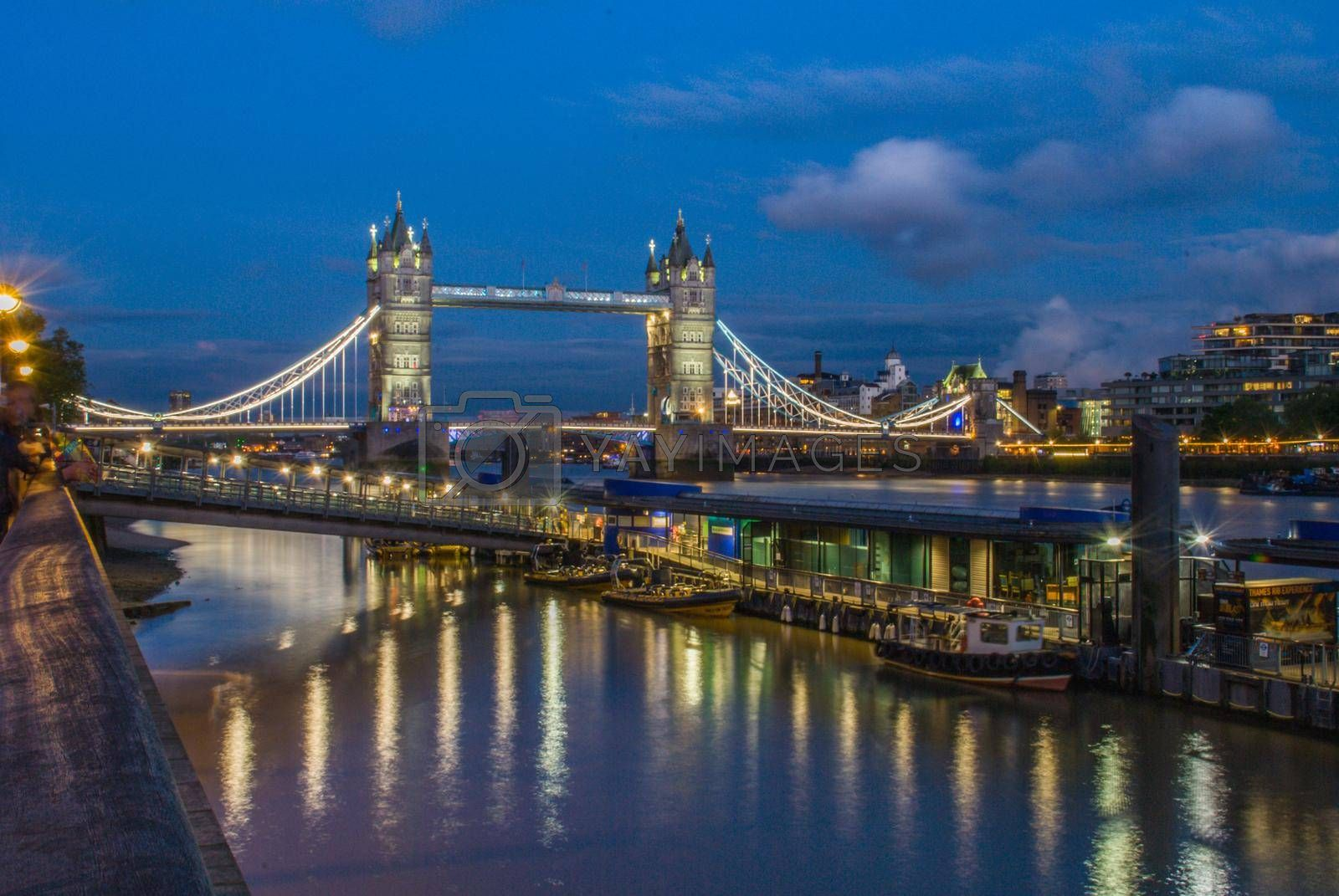 Night cityscape with Famous Tower Bridge in the evening with blue sky and reflex on water, London, England
