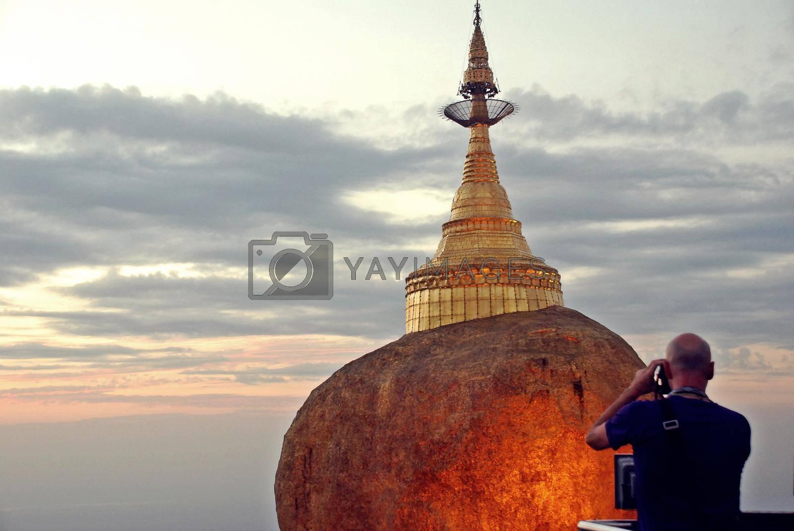 Tourists are taking pictures Golden rock is beautiful in the twilight , Kyaiktiyo Pagoda in Yangon, Myanmar