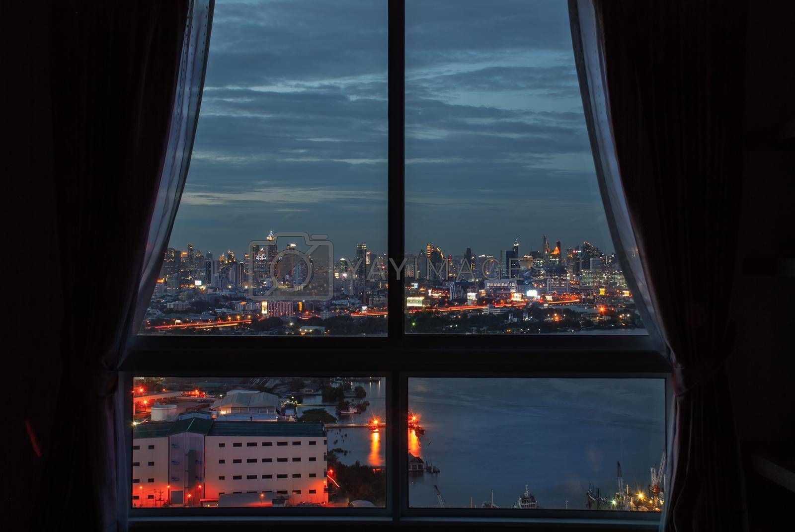 Bangkok, Thailand - 27 Aug, 2019 : The beautiful view of Bangkok, the beautiful skyscrapers along the Chao Phraya River during sunset seen through a bedroom window.