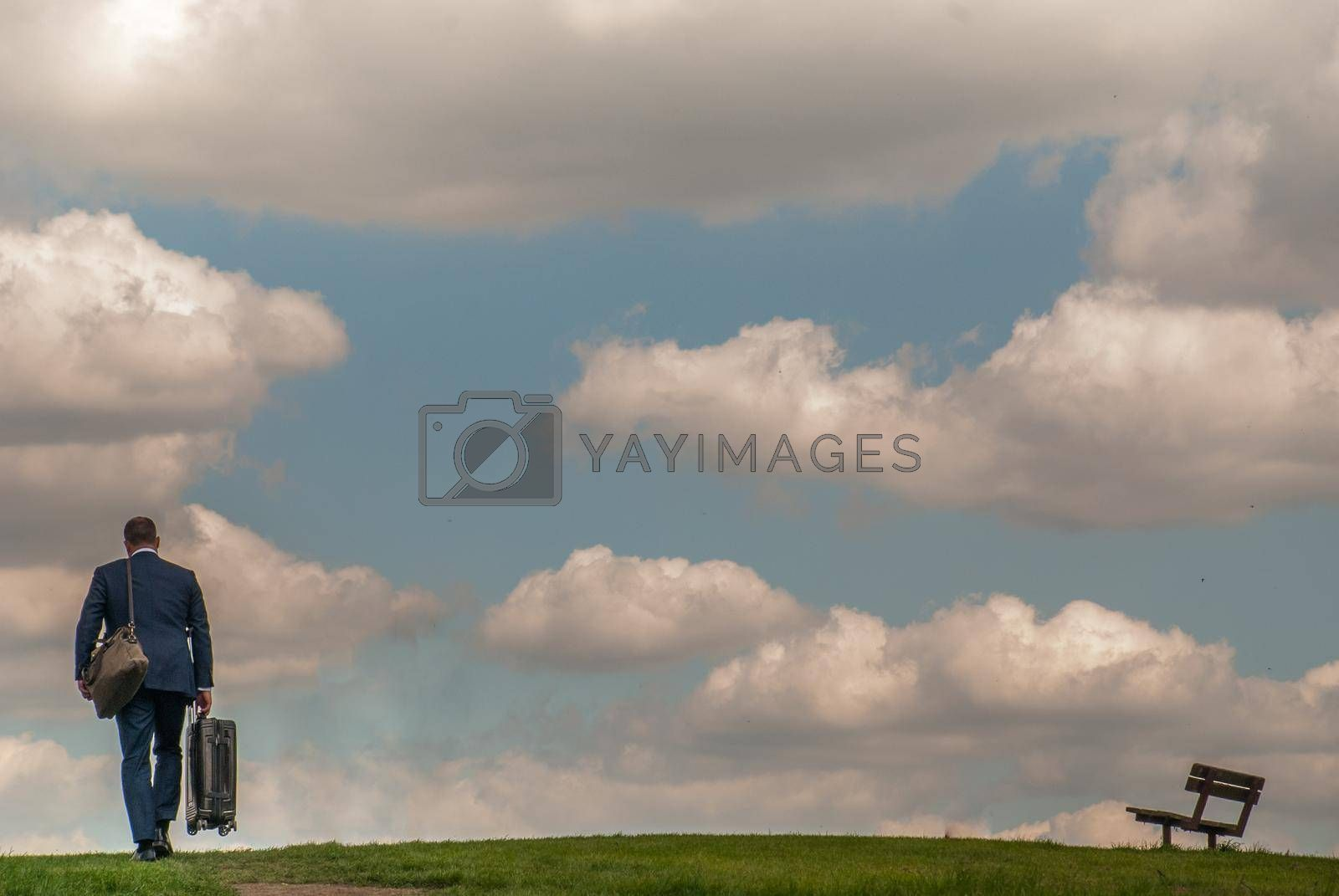 London - 21 May 2019 - Businessmen walking through the hills of Hampstead Heath with a beautiful sky backdrop.