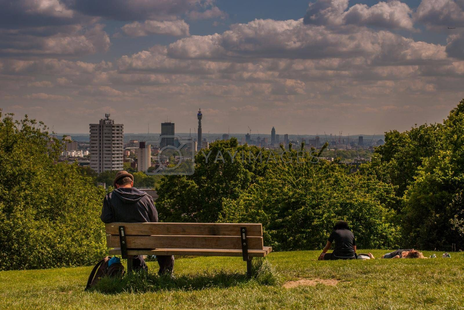 London - May 21, 2019 - A men sit on a wooden chair at Hampstead Heath with a beautiful city view backdrop.
