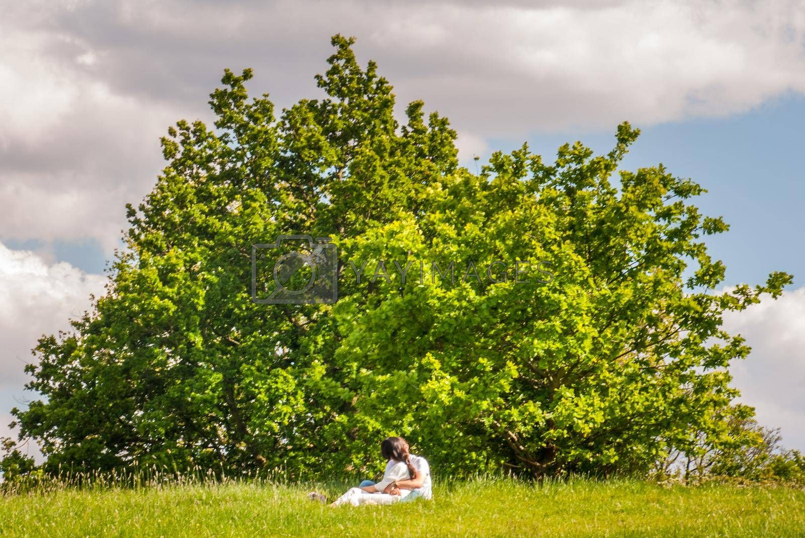 London - May 21, 2019 -  Beautiful couple of lovers on the lawn in Hampstead Heath, London.