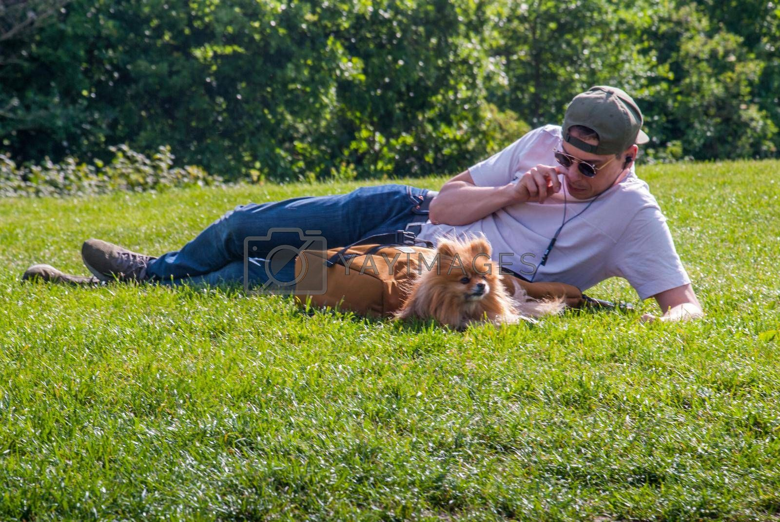 London - 21 May 2019 - A young man and a Cute Pomeranian dog chilling on green grass grass in the park.
