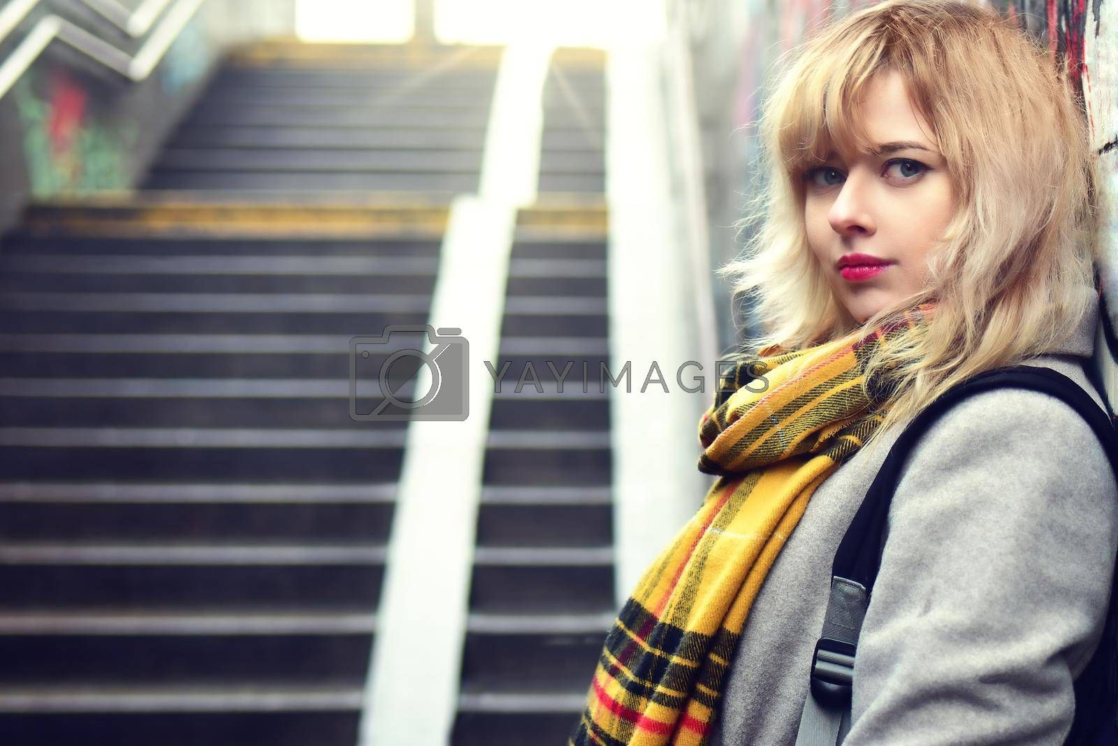 Royalty free image of Beautiful girl standing near a wall with graffiti in underground passage by Nickstock