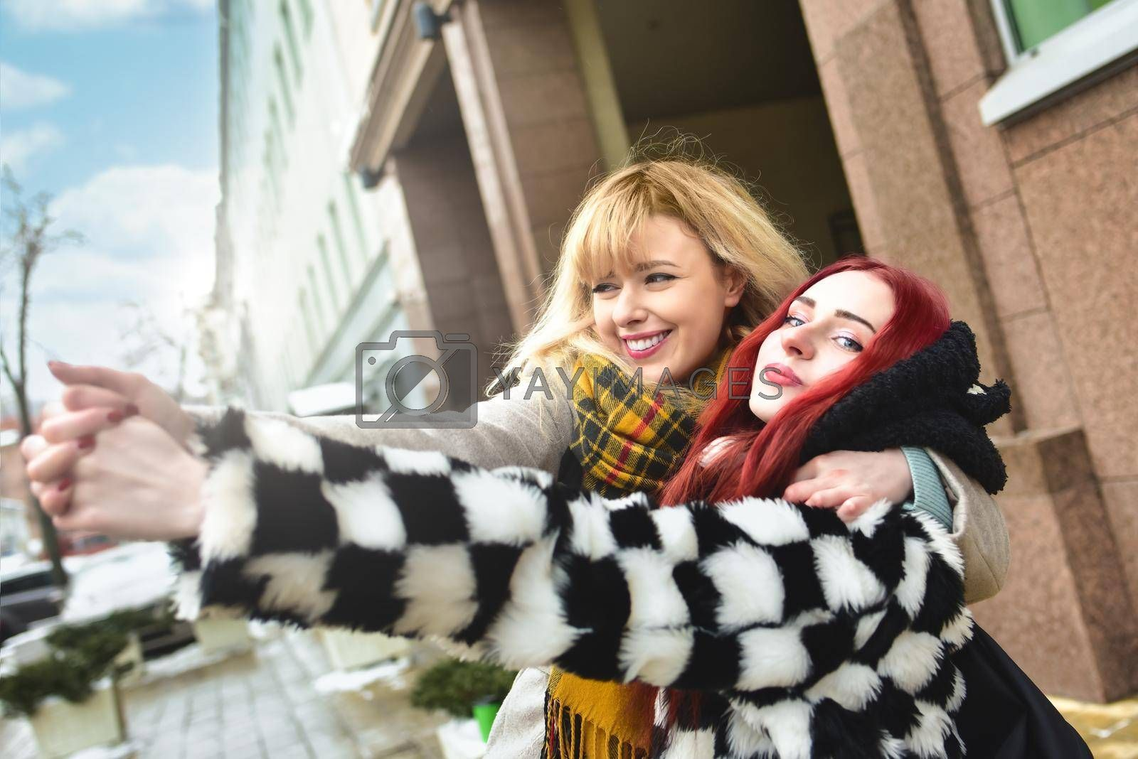Royalty free image of Young pretty girls best friends smiling and having fun, walking at the city. Shopping. Wearing stylish outerwear. Bright make up. Positive emotions. Outdoors lifestyle fashion close up portrait by Nickstock