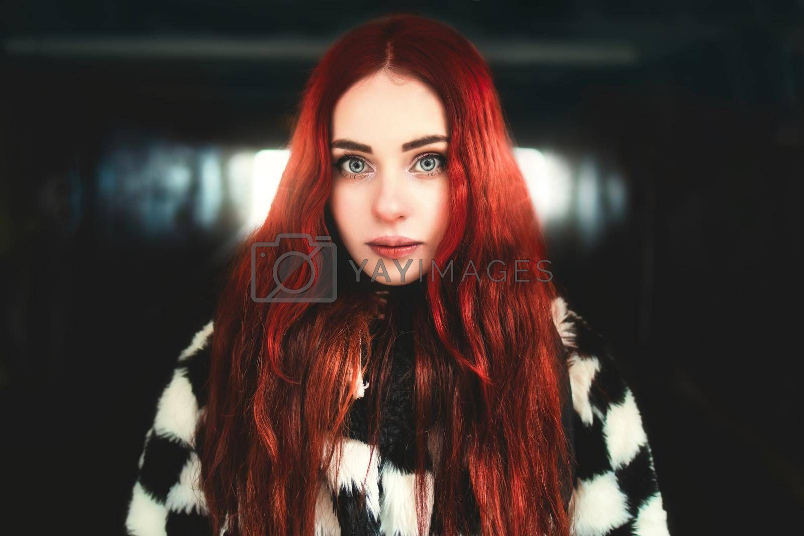 Royalty free image of beautiful woman with red hair standing in the underground passage by Nickstock