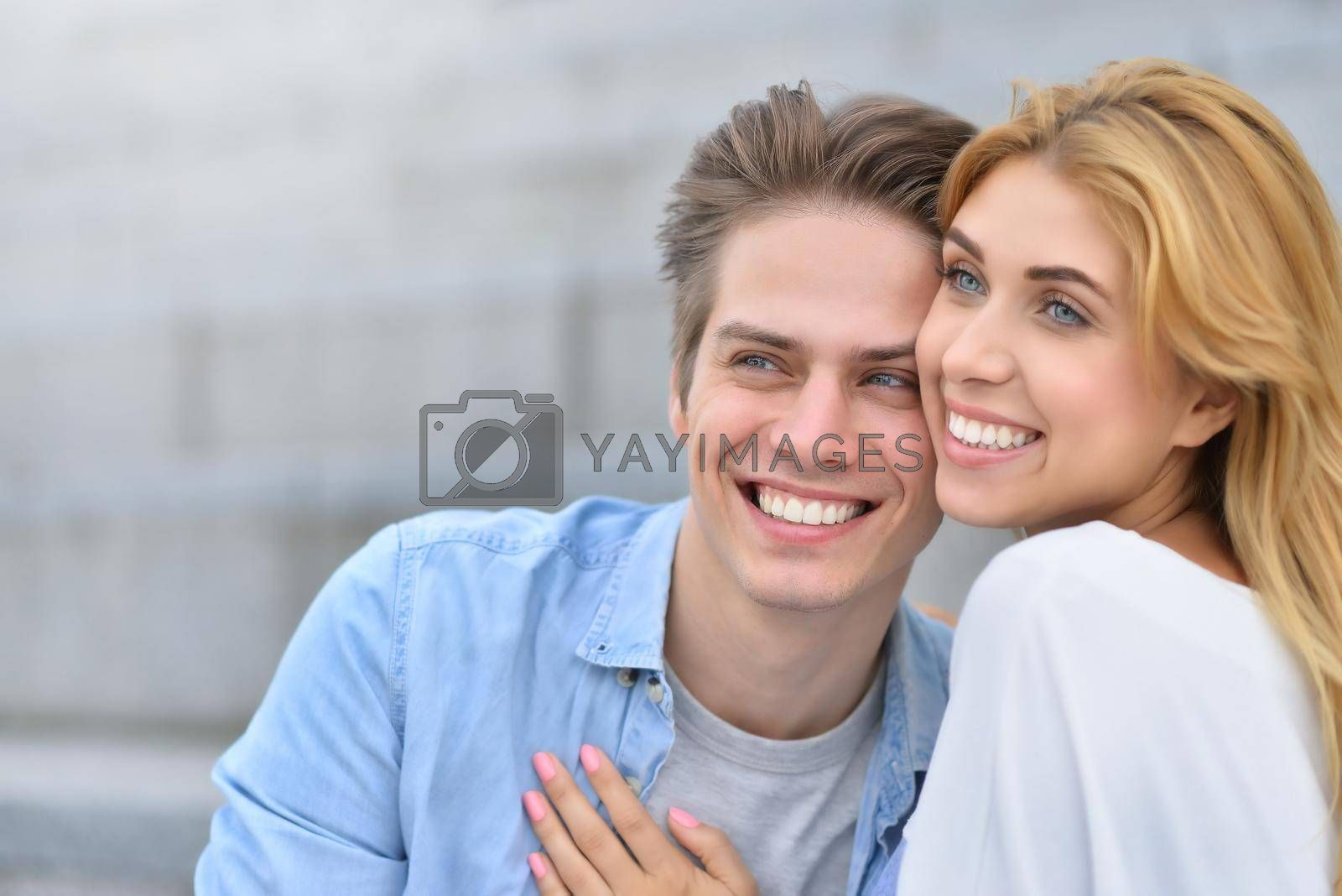 Royalty free image of Happy young couple hugging and laughing outdoors. by Nickstock