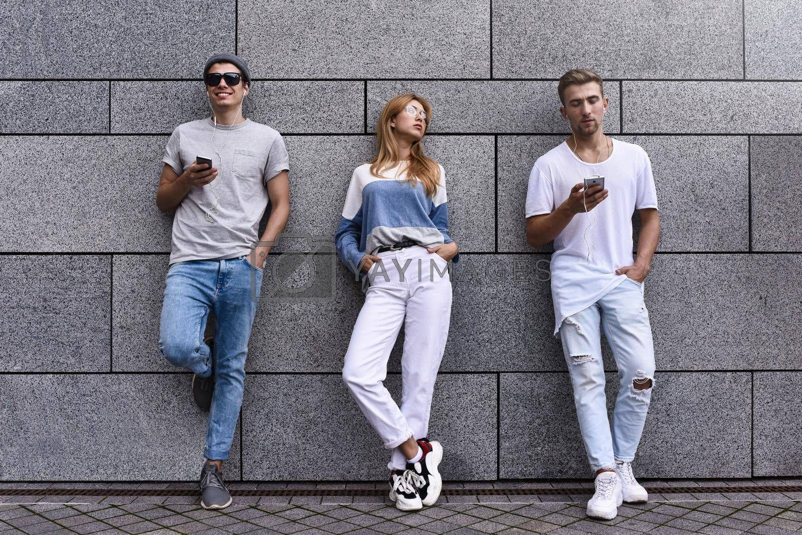 Royalty free image of Fashion portrait of Three best friends posing at street, wearing stylish outfit and jeans against gray wall . by Nickstock