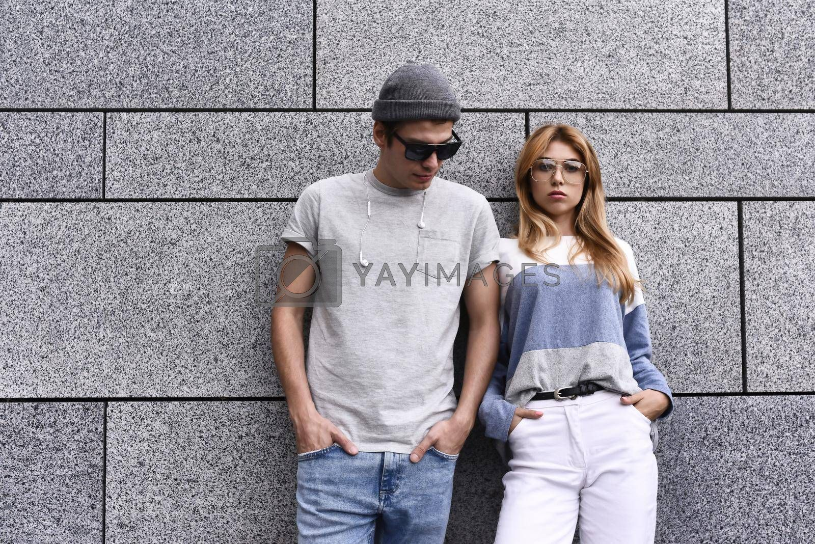 Royalty free image of Two friends leaning to a wall and ignoring each other. Technology addiction concept, guy and a woman in gray wall background. by Nickstock