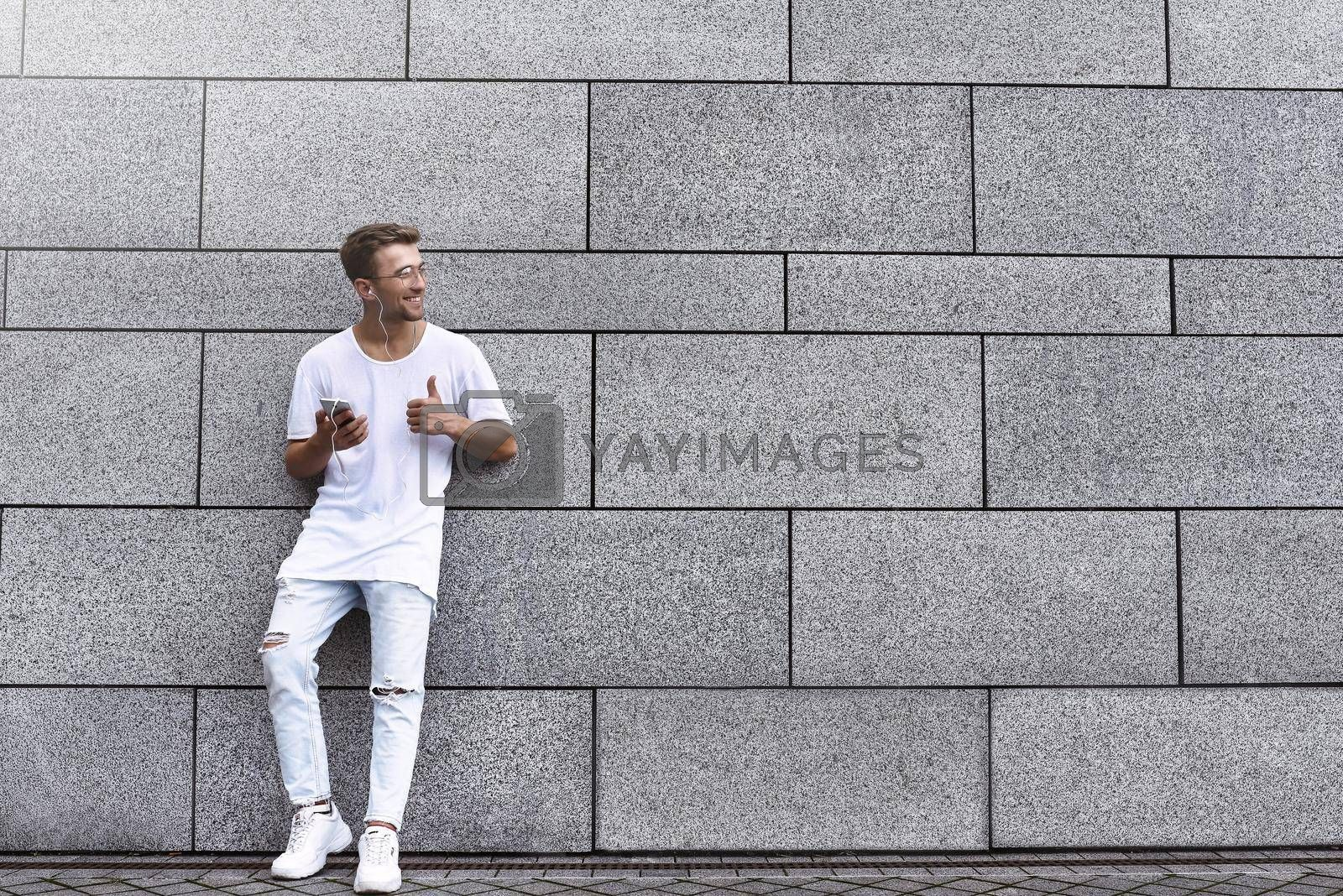 Royalty free image of Portrait of a handsome young man in casual clothes enjoying music on your mobile phone, against a brick wall. copy space by Nickstock