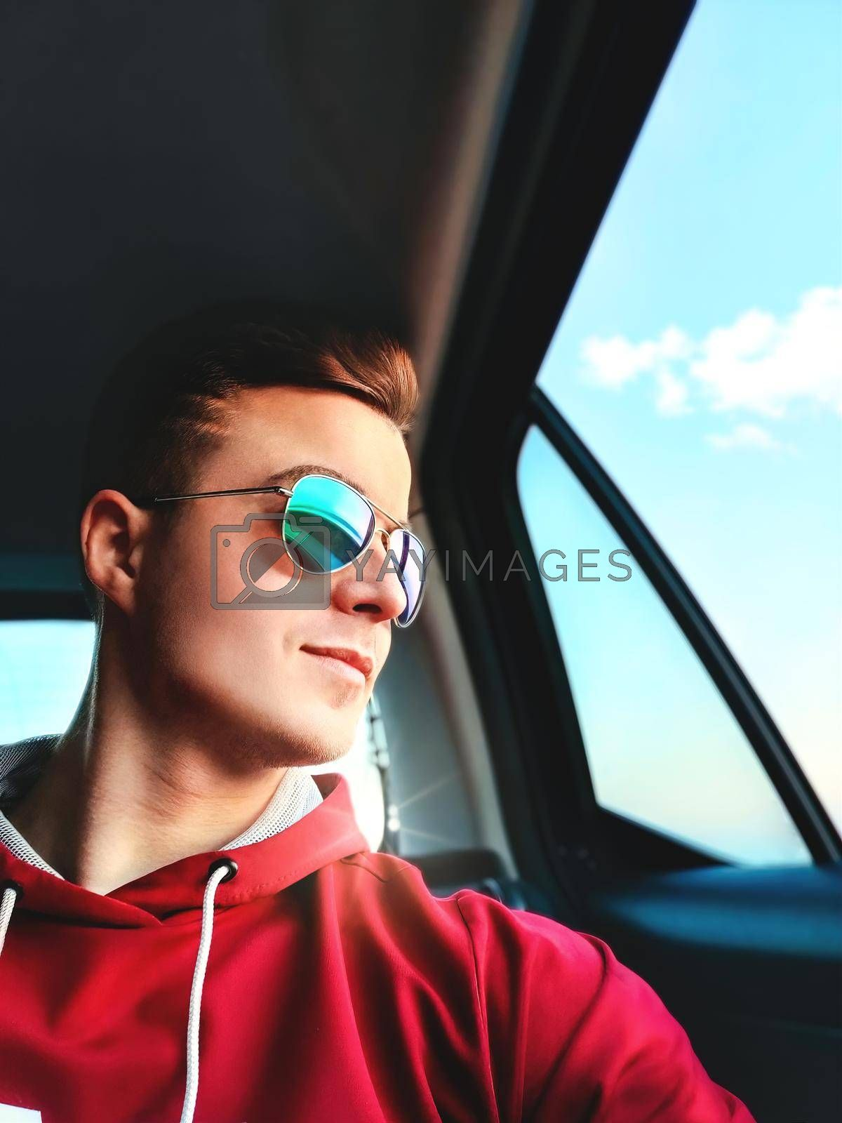 Royalty free image of A young man is sitting in the back seat of a taxi cab going to the airport and taking selfie by Nickstock