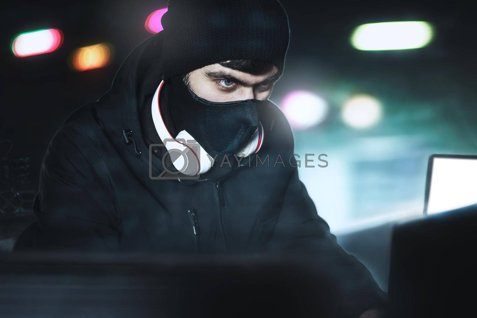 Royalty free image of Angry computer hacker weared balaclava stealing data from laptop in front of black background and blue light. close portrait. by Nickstock