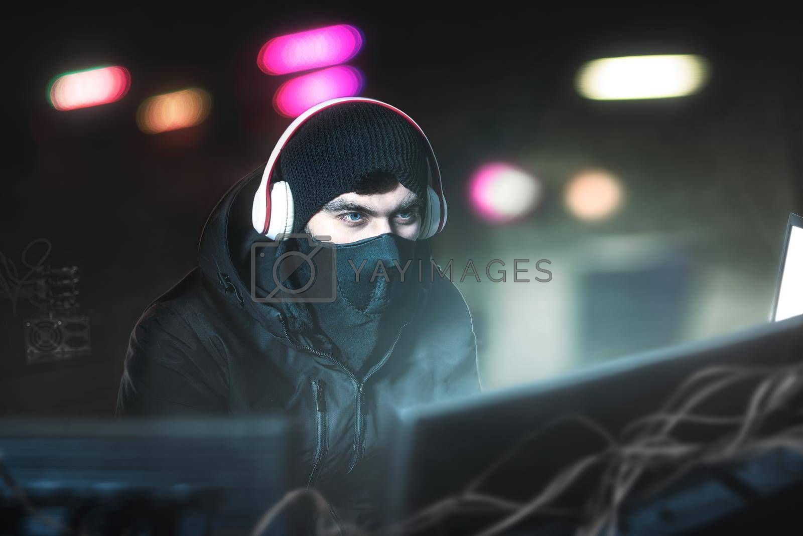 Royalty free image of Hacker in the office with headphones with microphone in search of prey. Steals data and copy of Bank. by Nickstock