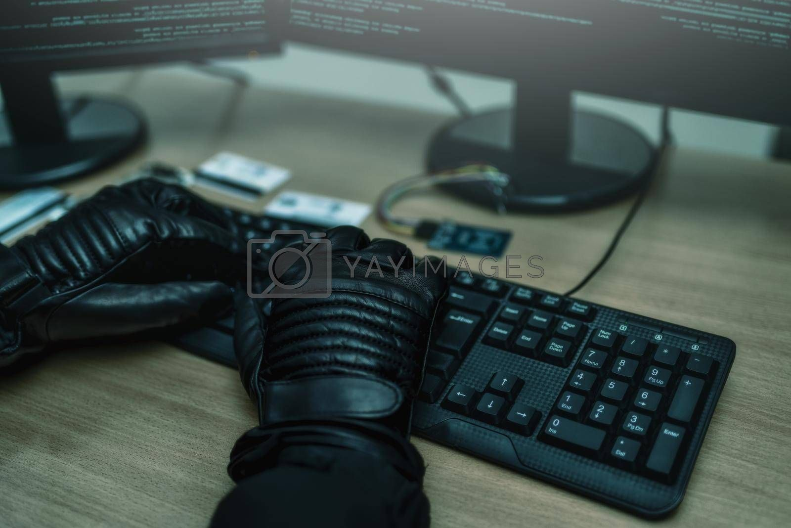 Royalty free image of Shot from the Back to Hacker Breaking into Corporate Data Servers from His Underground Hideout. close view of hackers hands by Nickstock