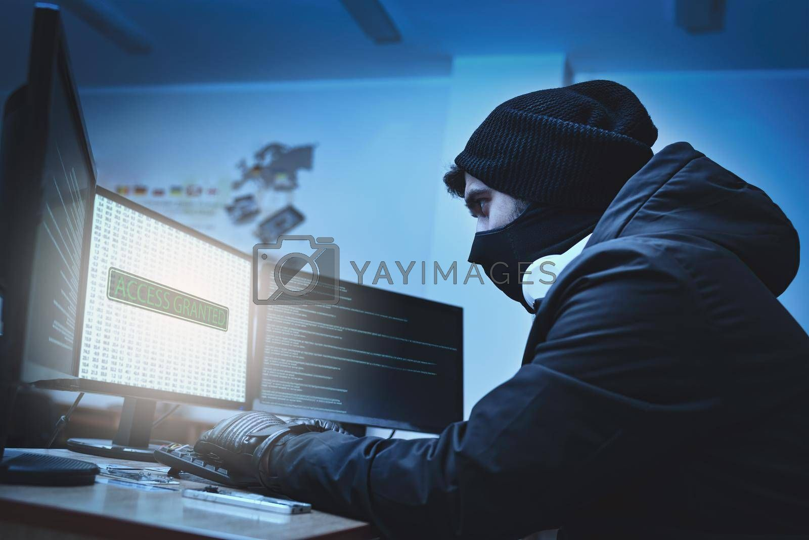 Royalty free image of Side view of a hacker hacking into corporate data servers from his underground hideout. The place has a dark atmosphere, lots of displays by Nickstock