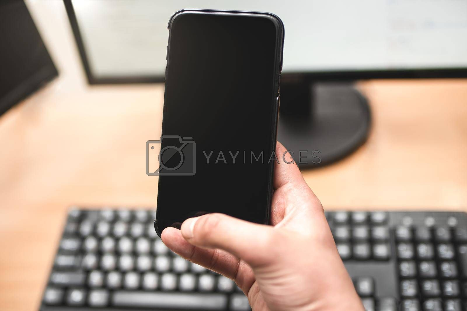 Royalty free image of Person holding a smart phone and pointing her finger at the blank screen against a computer keyboard,monitor on wooden table. business concept by Nickstock