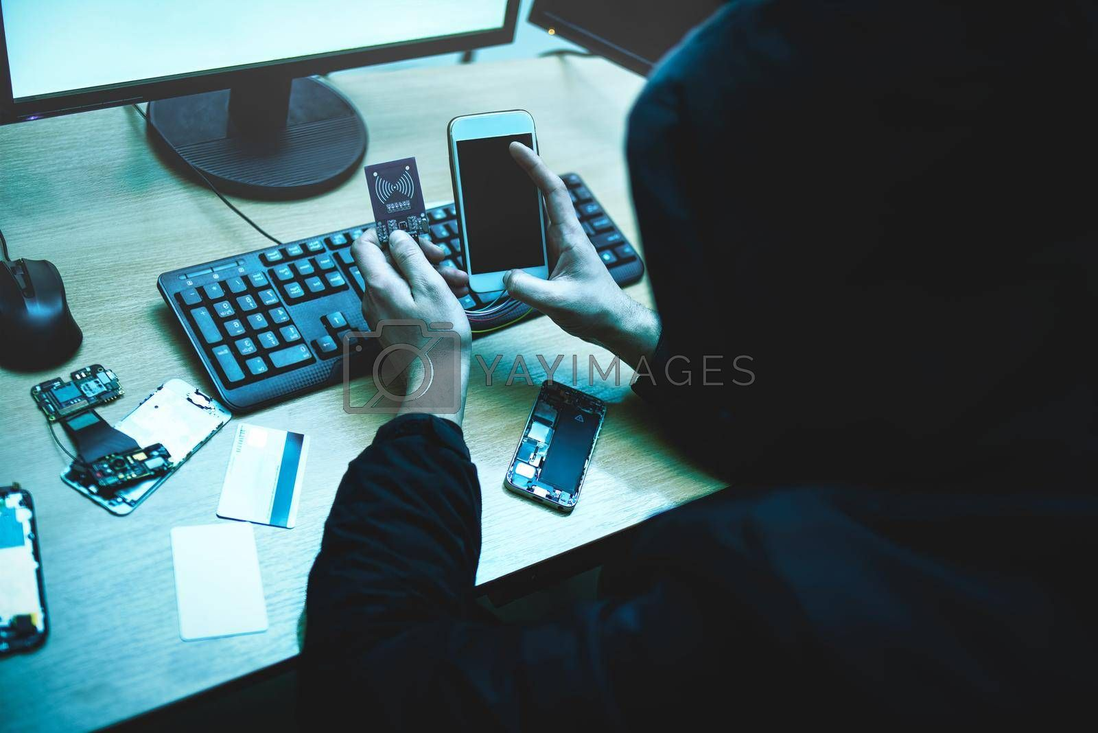 Royalty free image of Male hacker is trying to access the phone. Security and protection of personal data. The concept of cyber crime and hacking by Nickstock