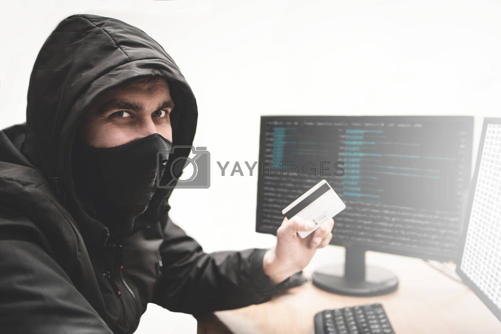 Royalty free image of Cunning fraudster hacker in white background with stolen credit card in hand tries to steal money from bank account by Nickstock