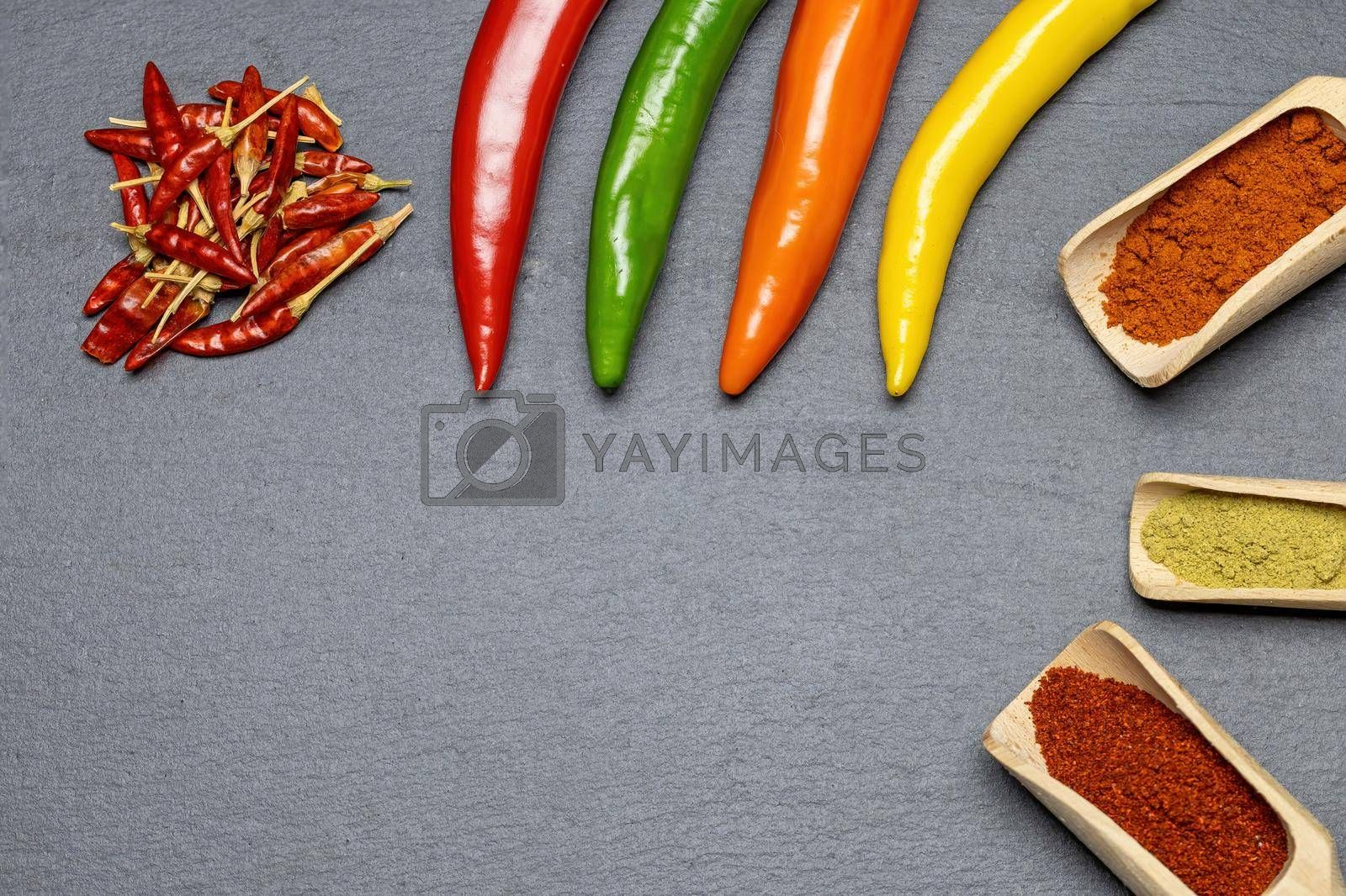 Royalty free image of Different types of fresh, dried and ground chili on the desk. by Frank11