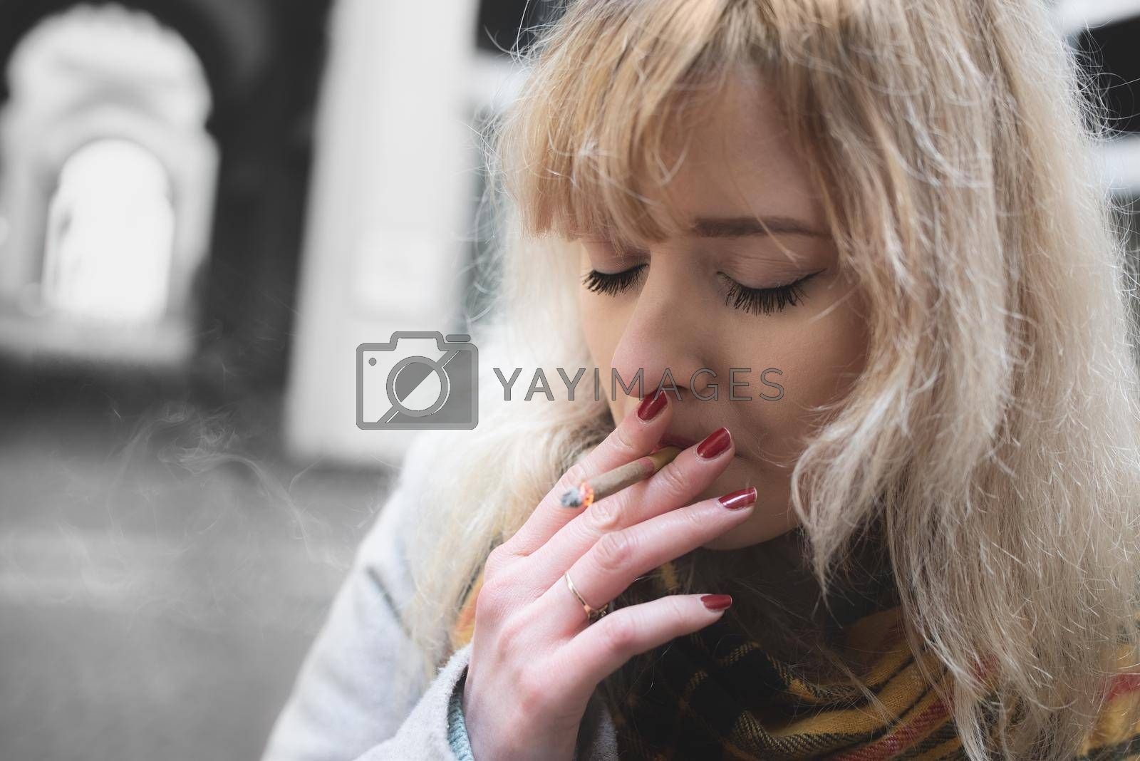 Royalty free image of serious young blond woman on gray background smoking with closed eyes by Nickstock
