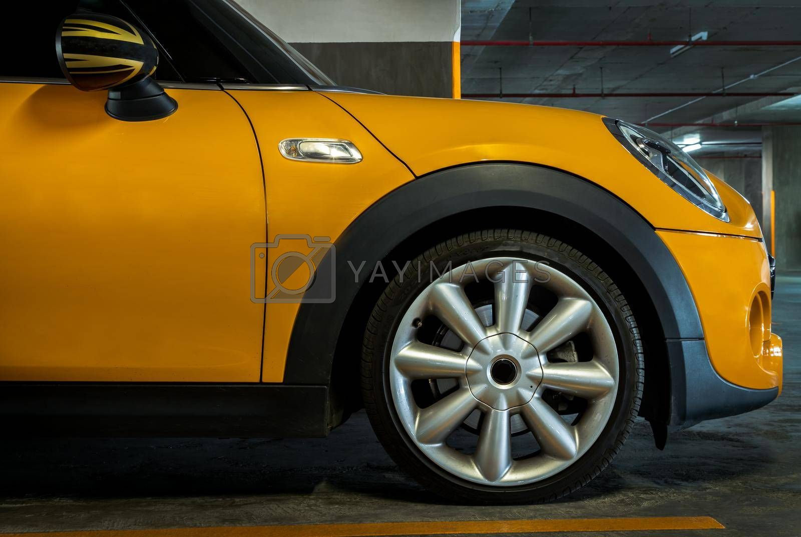 Bangkok, Thailand - 27 May 2021 : Side view of Headlights, Wheel, Hood, Sidelights and Side view mirror of Yellow car. Selective focus.