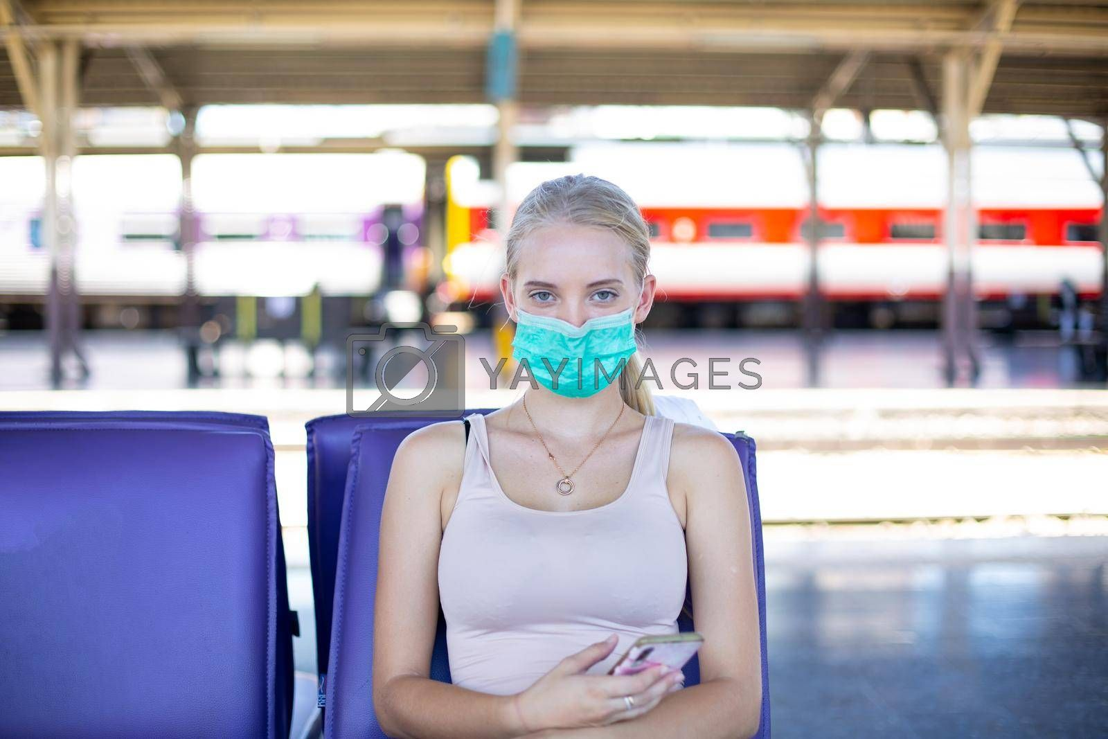 young woman with face mask waiting in vintage train, relaxed and carefree at the station platform in Bangkok, Thailand before catching a train. Travel photography. Lifestyle.