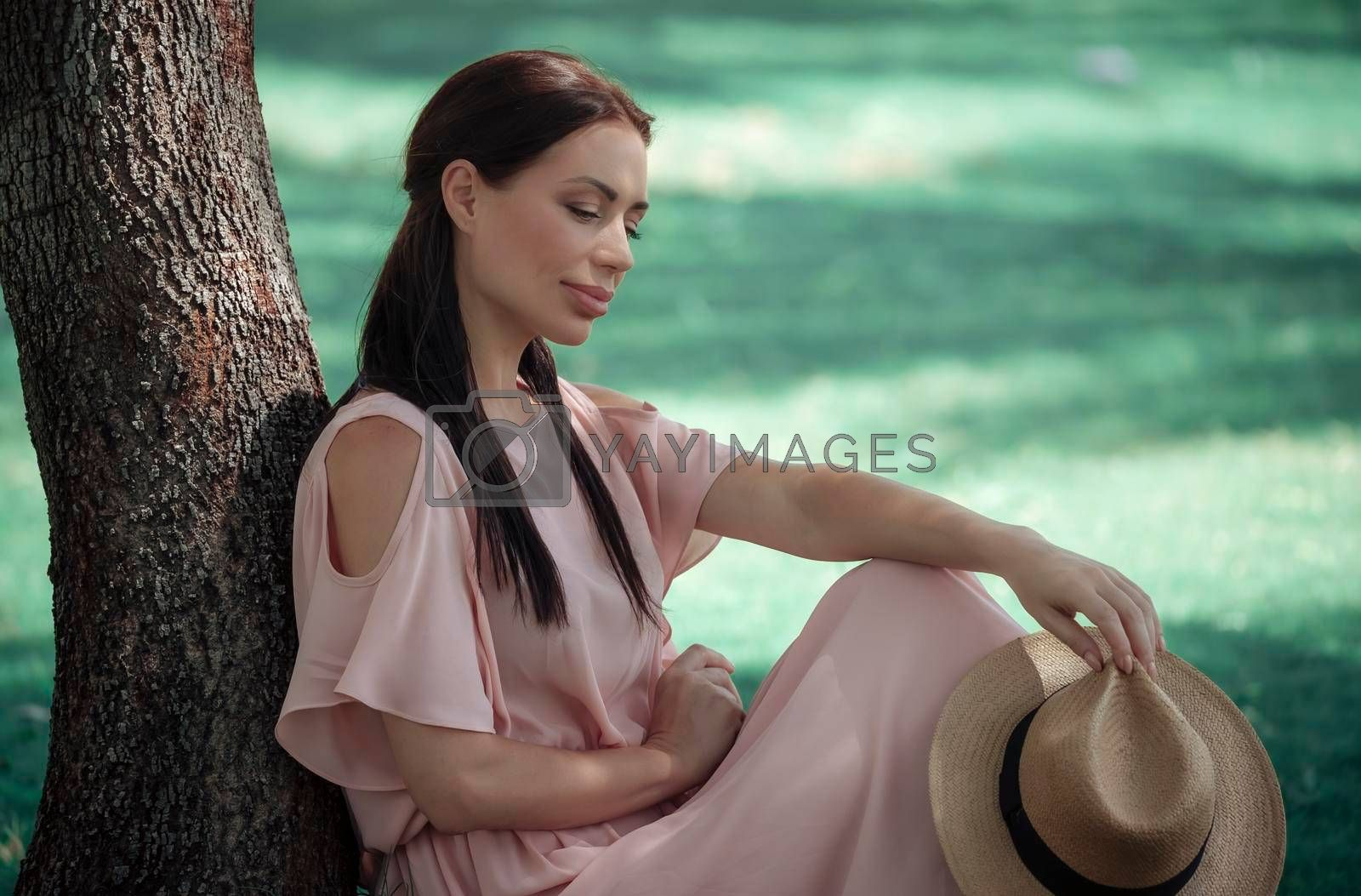 Beautiful Young Female Spending Leisure Time in the Park. Resting near the Tree with Strow Sun Hat in Hand. Happy Life.