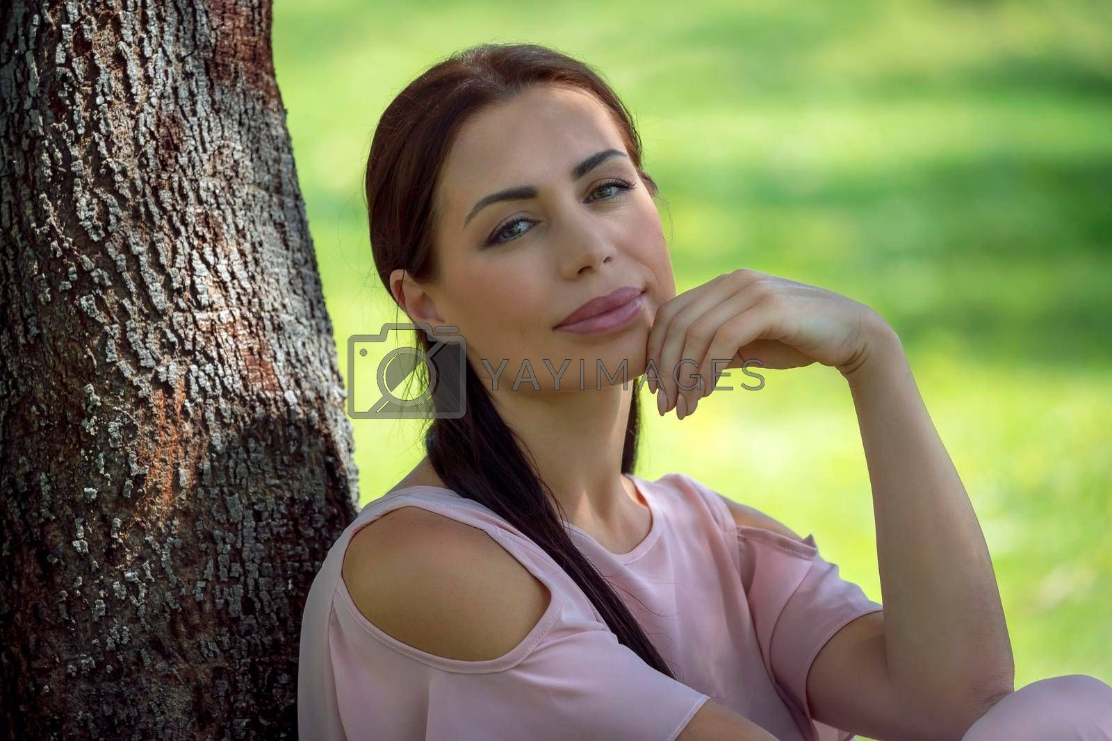Portrait of a Beautiful Young Woman Sitting Near the Tree on the Meadow in the Park. Spending Warm Sunny Day Outdoors. Happy Summer Weekend.