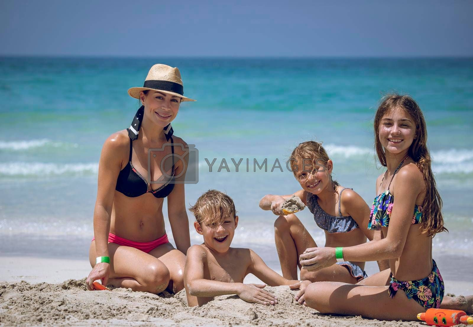 Portrait of Big Happy Family. Beautiful Mother with Three Kids Having Fun on the Beach. Playing Games in Sand. Spending Summer Holidays Together.
